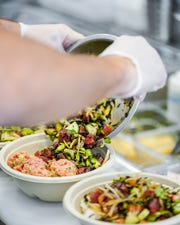 A chef pours topping mixture over a poke bowl.