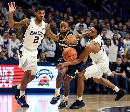 Penn State's Myles Dread (2) and Josh Reaves (23) knock the ball away from Michigan's Zavier Simpson during the first half Tuesday in State College, Pa.