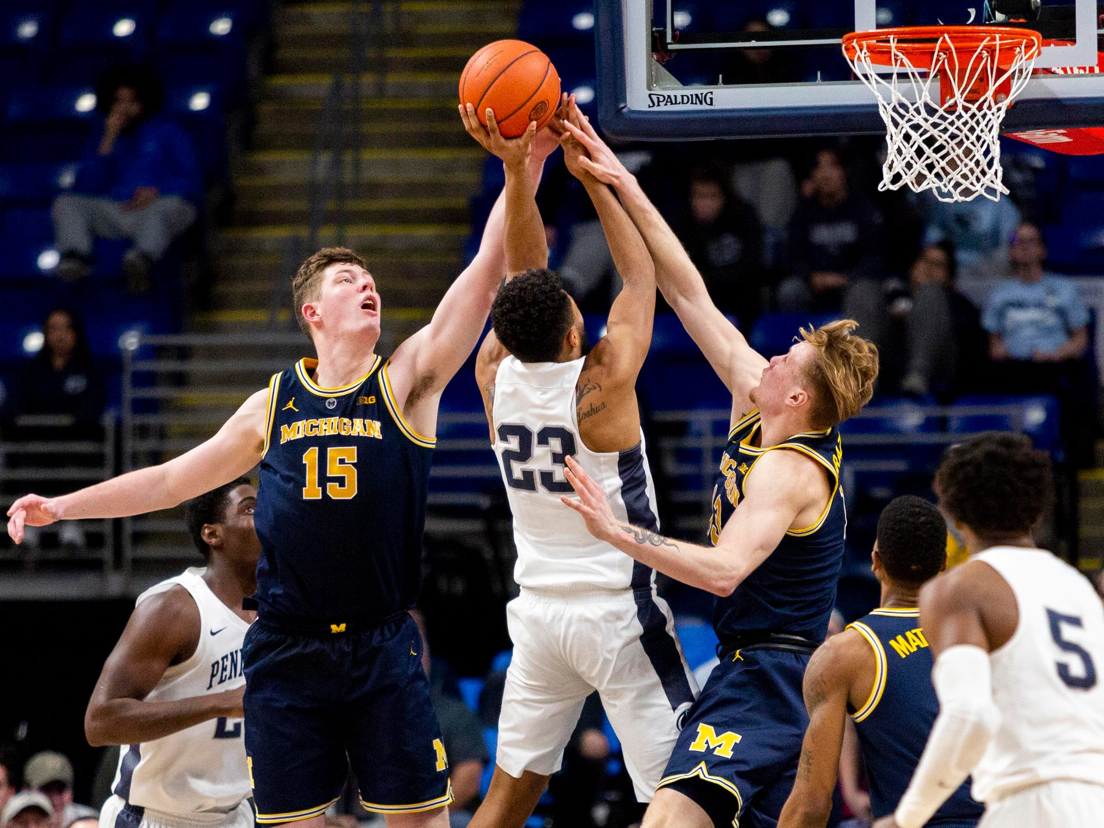 Penn State guard Josh Reaves attempts to shoot the ball past Michigan center Jon Teske, left, and forward Ignas Brazdeikis during the second half of U-M's 75-69 loss on Tuesday, Feb. 12, 2019, in State College, Pa.