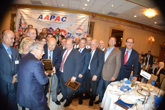 U.S. House. Rep. John Dingell (D-Dearborn) is honored in Dearborn by the Arab American Political Action Committee (AAPAC) on Oct. 29, 2014. He is handed a plaque by Osama Siblani, publisher of the Arab-American News and a leader with AAPAC. On Dingell's right is Detroit Mayor Mike Duggan. Other Arab-American and Muslim leaders are in the photo.