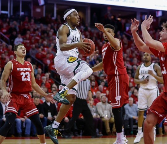 Cassius Winston looks to pass as Wisconsin's Charles Thomas defends during the first half Tuesday in Madison, Wis.