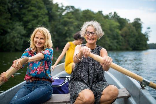 Women rowing boat in lake.