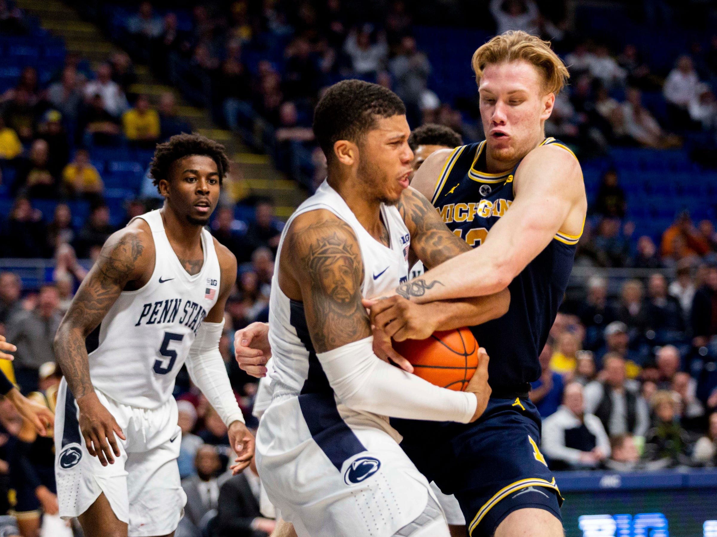 Michigan forward Ignas Brazdeikis battles for a rebound with Penn State guard Myles Dread during the second half Tuesday, Feb. 12, 2019, in State College, Pa.
