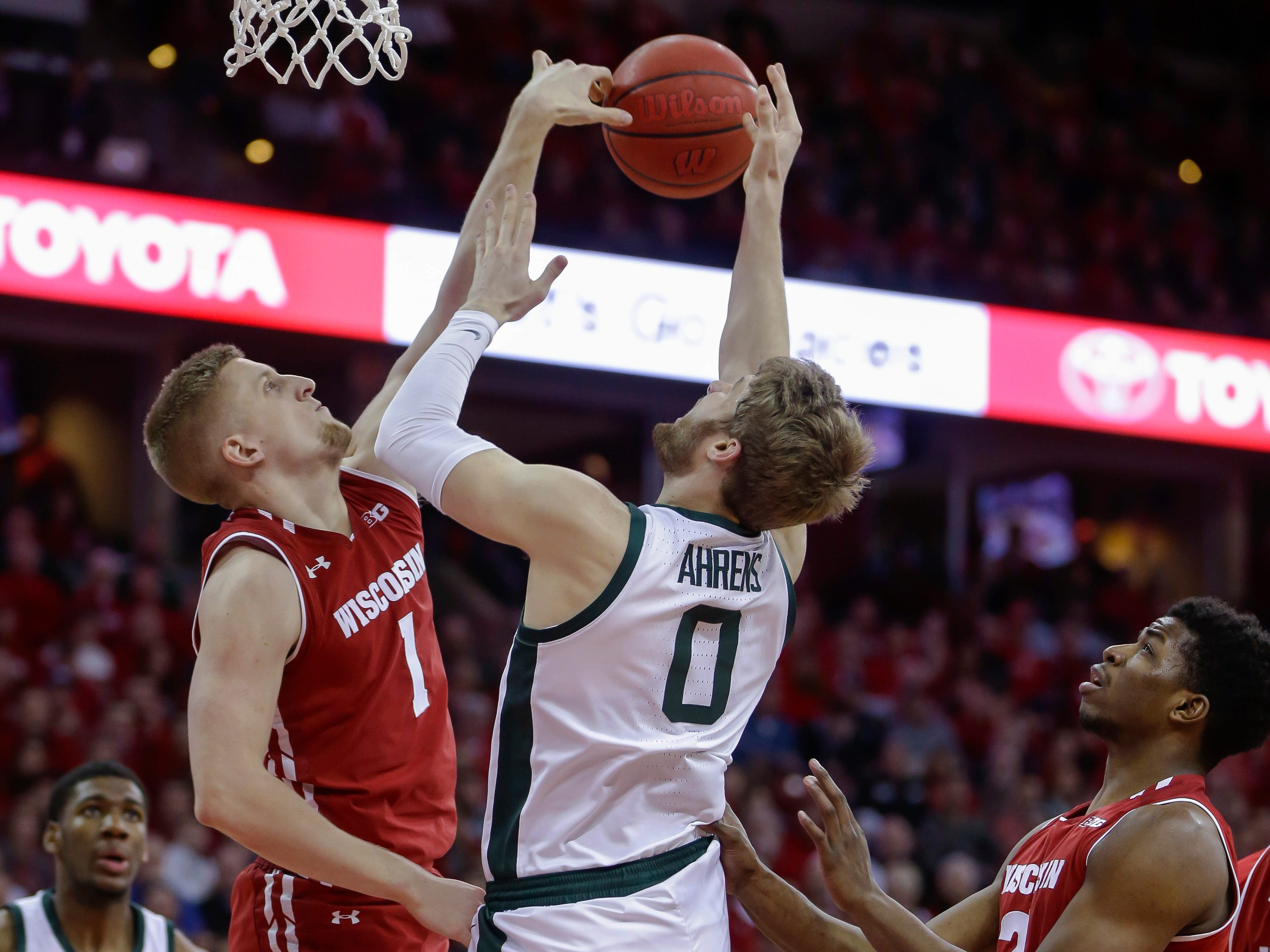 Wisconsin's Brevin Pritzl (1) blocks a shot by Michigan States's Kyle Ahrens (0) during the first half.