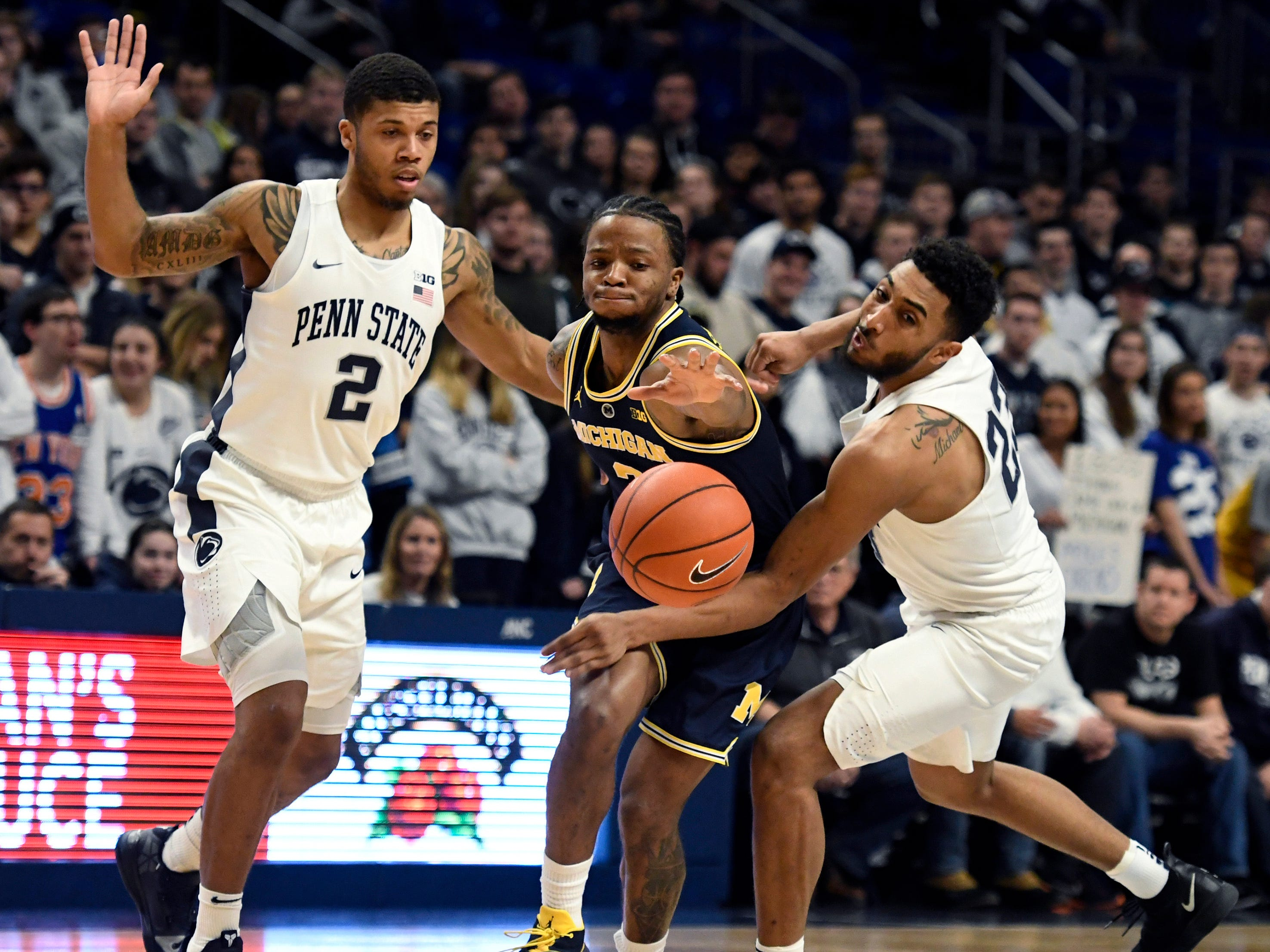 Penn State guard Myles Dread (2) and Penn State guard Josh Reaves (23) try to get the ball away from Michigan guard Zavier Simpson (3) during the first half of an NCAA college basketball game, Tuesday, Feb. 12, 2019, in State College, Pa.