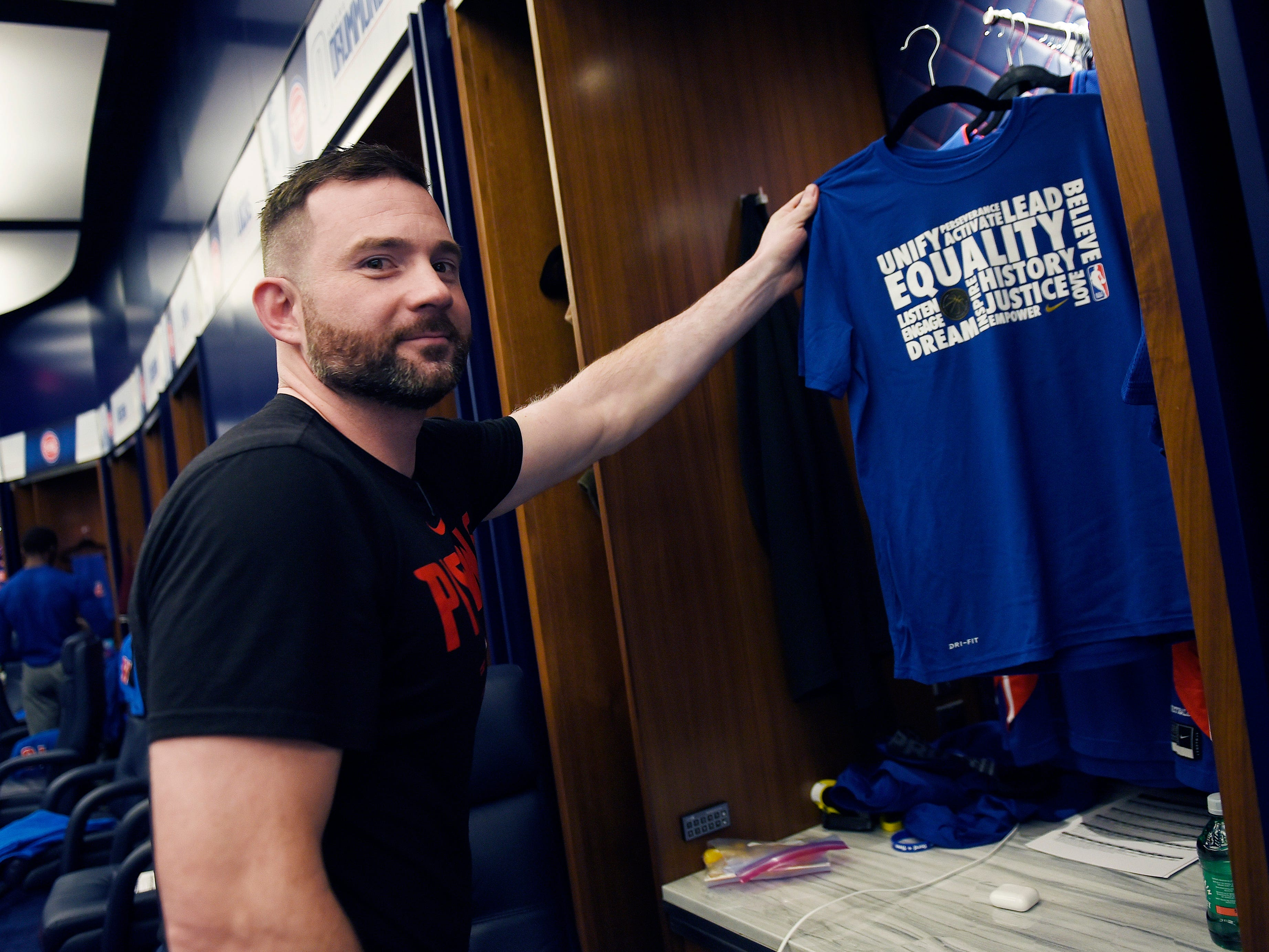 John Coumoundouros, equipment manager, hangs a Black History Month T-shirt in Blake Griffin's locker before the game. He and his staff are responsible for all game-day equipment needs of the players.
