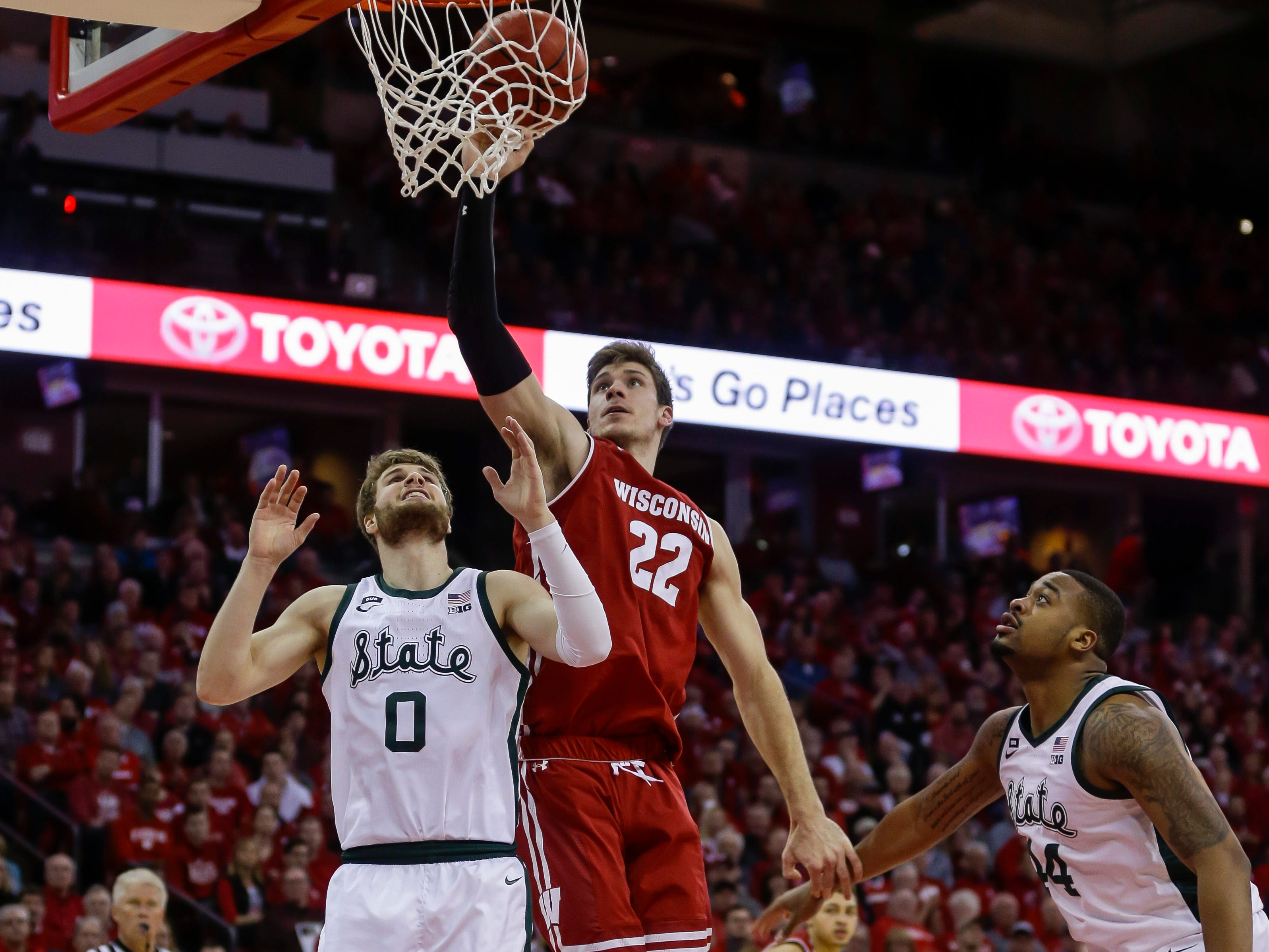 Wisconsin's Ethan Happ (22) shoots against Michigan States's Kyle Ahrens (0) and Nick Ward, right, during the second half.