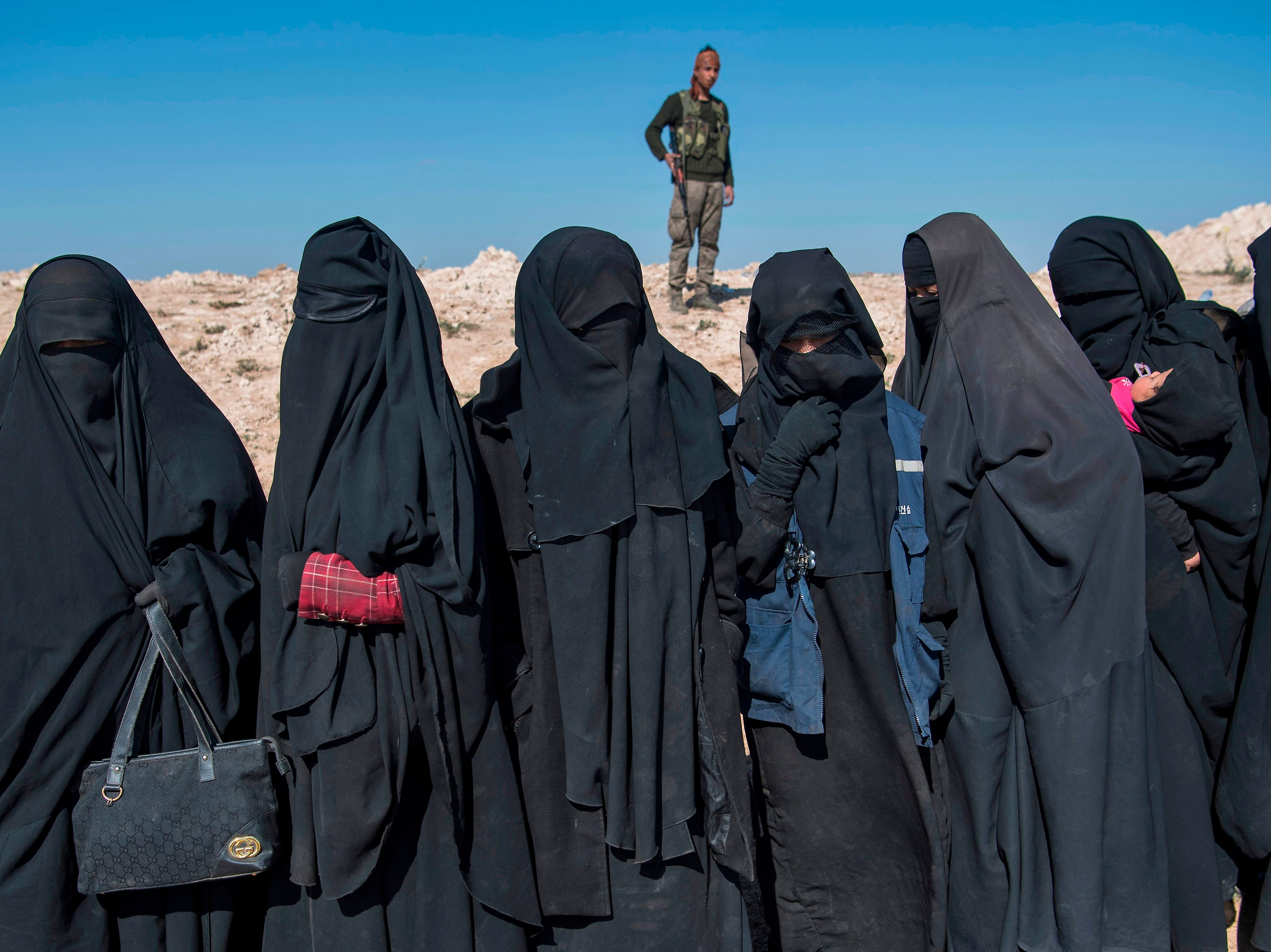 """A fighter with the U.S.-backed Syrian Democratic Forces keeps watch near veiled women standing on a field after they fled from the Baghouz area in the eastern Syrian province of Deir Ezzor on Feb. 12, 2019 during an operation to expel hundreds of Islamic State group  jihadists from the region. Syrian fighters backed by artillery fire from a U.S.-led coalition battled a fierce jihadist counteroffensive as they pushed to retake a last morsel of territory from the Islamic State group in an assault lasting days. More than four years after the extremists declared a """"caliphate"""" across large parts of Syria and neighboring Iraq, several offensives have whittled that down to a tiny scrap of land in eastern Syria."""