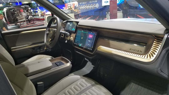 The interior of the Rivian R1T pickup featues big, digital screens and generous use of wood trim. In addition to 400 miles of range the truck offers Level 3 autonomous driving.