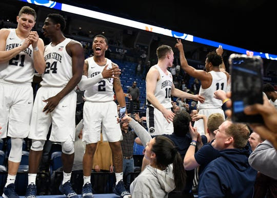 Penn State players John Harrar (21), Mike Watkins (24), Myles Dread (2), Kyle McCloskey (10) and Lamar Stevens (11) celebrate their team's upset win over Michigan.