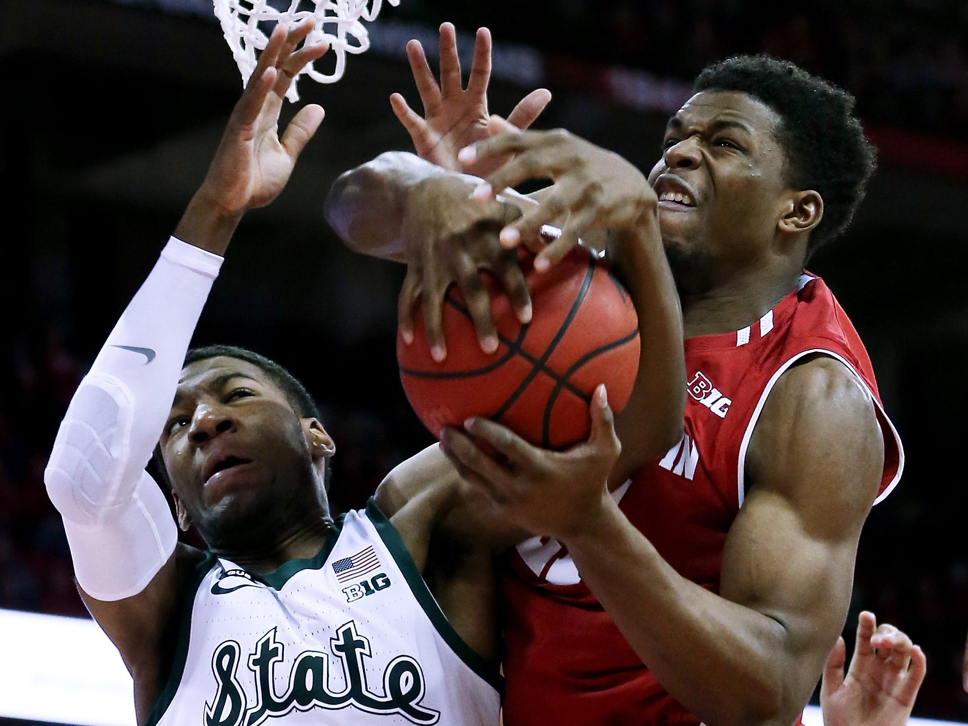 Michigan State's Aaron Henry (11) and Wisconsin's Khalil Iverson battle for a rebound in the first half.