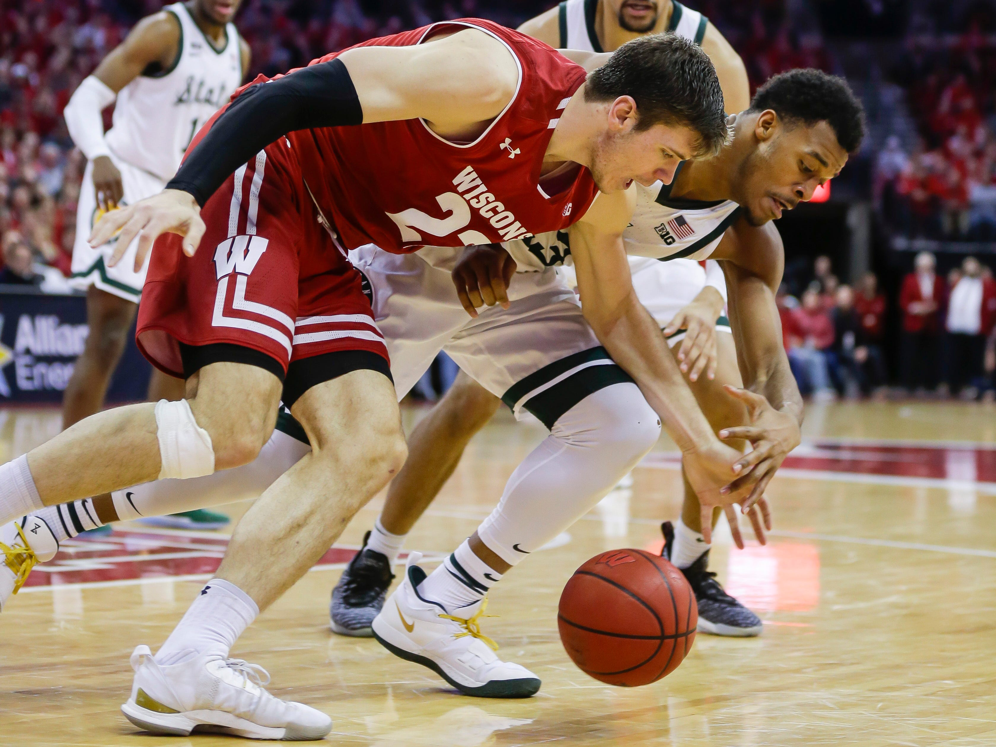 Wisconsin's Ethan Happ (22) and Michigan States's Xavier Tillman go after a loose ball during the second half.