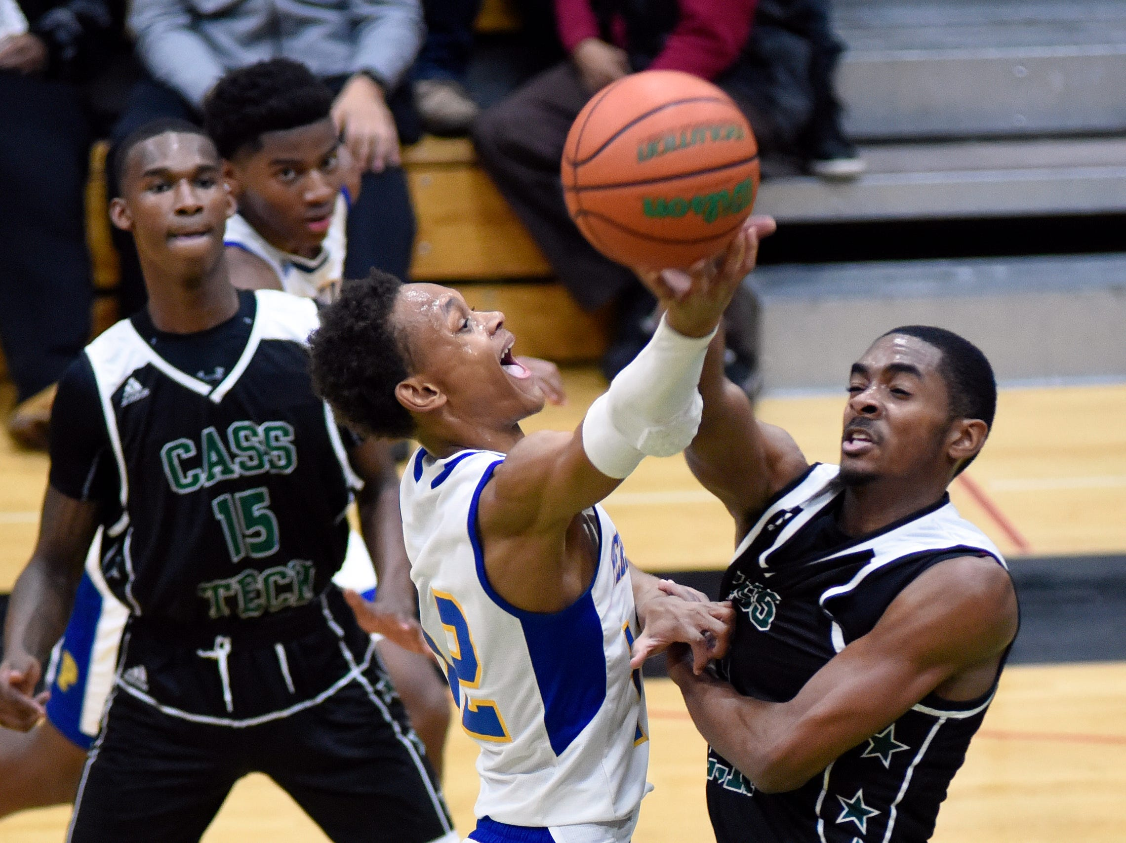 Cass Tech's Kalil Whitehead (23) blocks the shot of Detroit Pershing's Pierre Hill (12) during the second quarter.