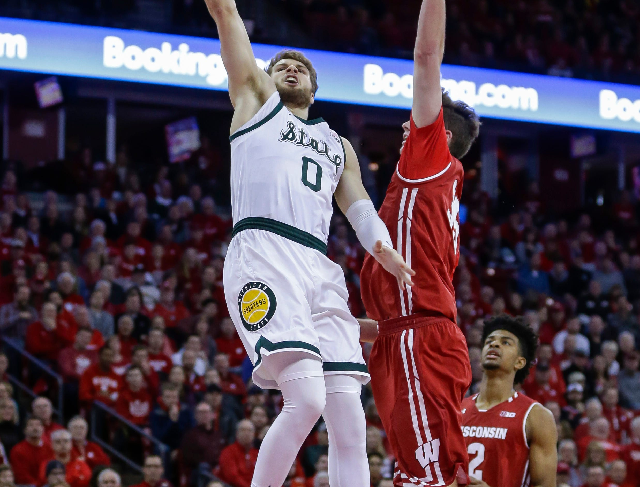 Michigan States's Kyle Ahrens (0) shoots against Wisconsin's Nate Reuvers (35) during the first half of an NCAA college basketball game Tuesday, Feb. 12, 2019, in Madison, Wis. (AP Photo/Andy Manis)