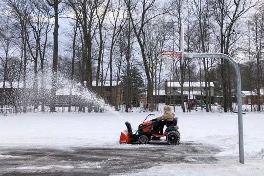 Tasha Pettas snow covers basketball court in Elementary Forest school in Farmington County, February 13, 2019. Pettas works for D.M. Burr facilities management that contracts with Public Farmington schools.