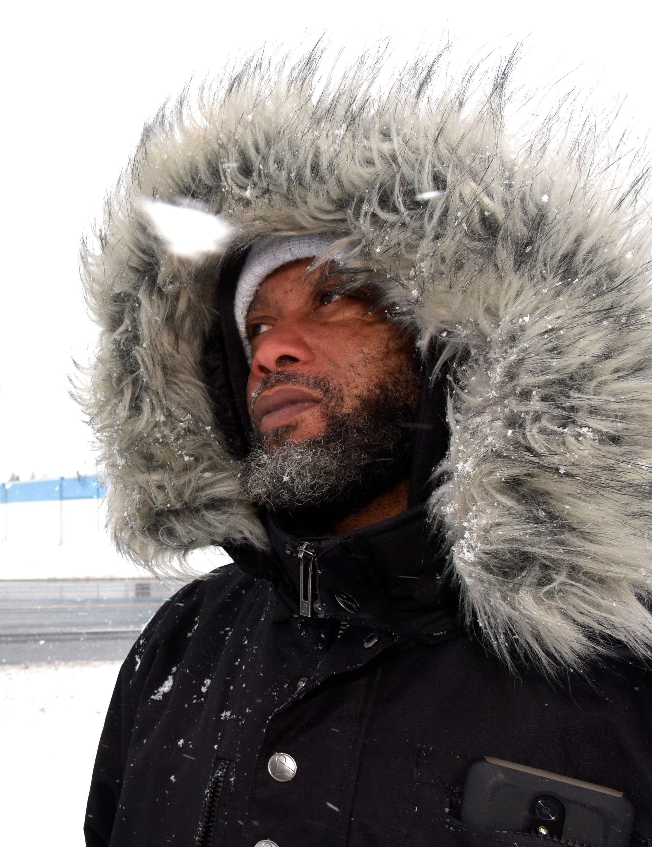 Paul Hurst, of Clinton Township, braces against the cold wind and snow while waiting for a SMART bus in Sterling Heights, Wednesday morning, February 13, 2019.