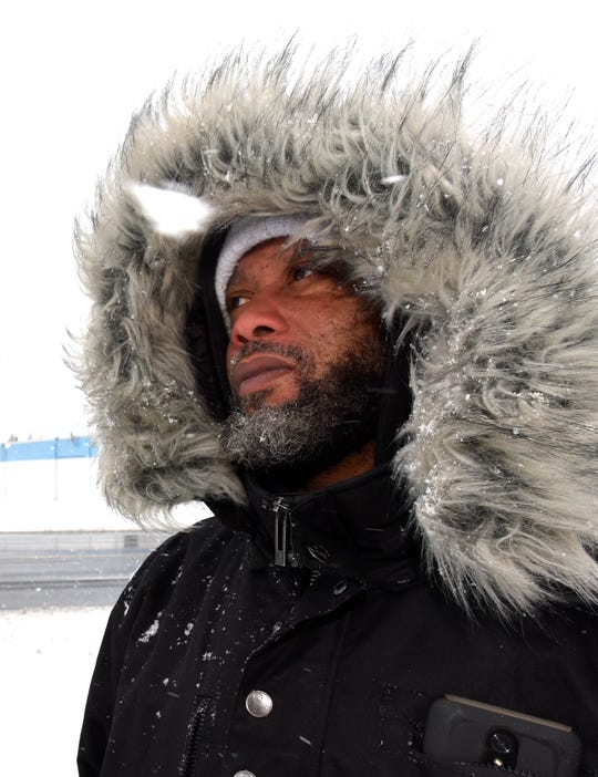 Paul Hurst of Clinton Township braces against the cold wind and snow while waiting for a SMART bus in Sterling Heights on Wednesday morning, Feb. 13, 2019.