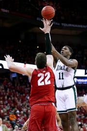 Aaron Henry of the Michigan State Spartans attempts a shot while being guarded by Ethan Happ of the Wisconsin Badgers in the first half.