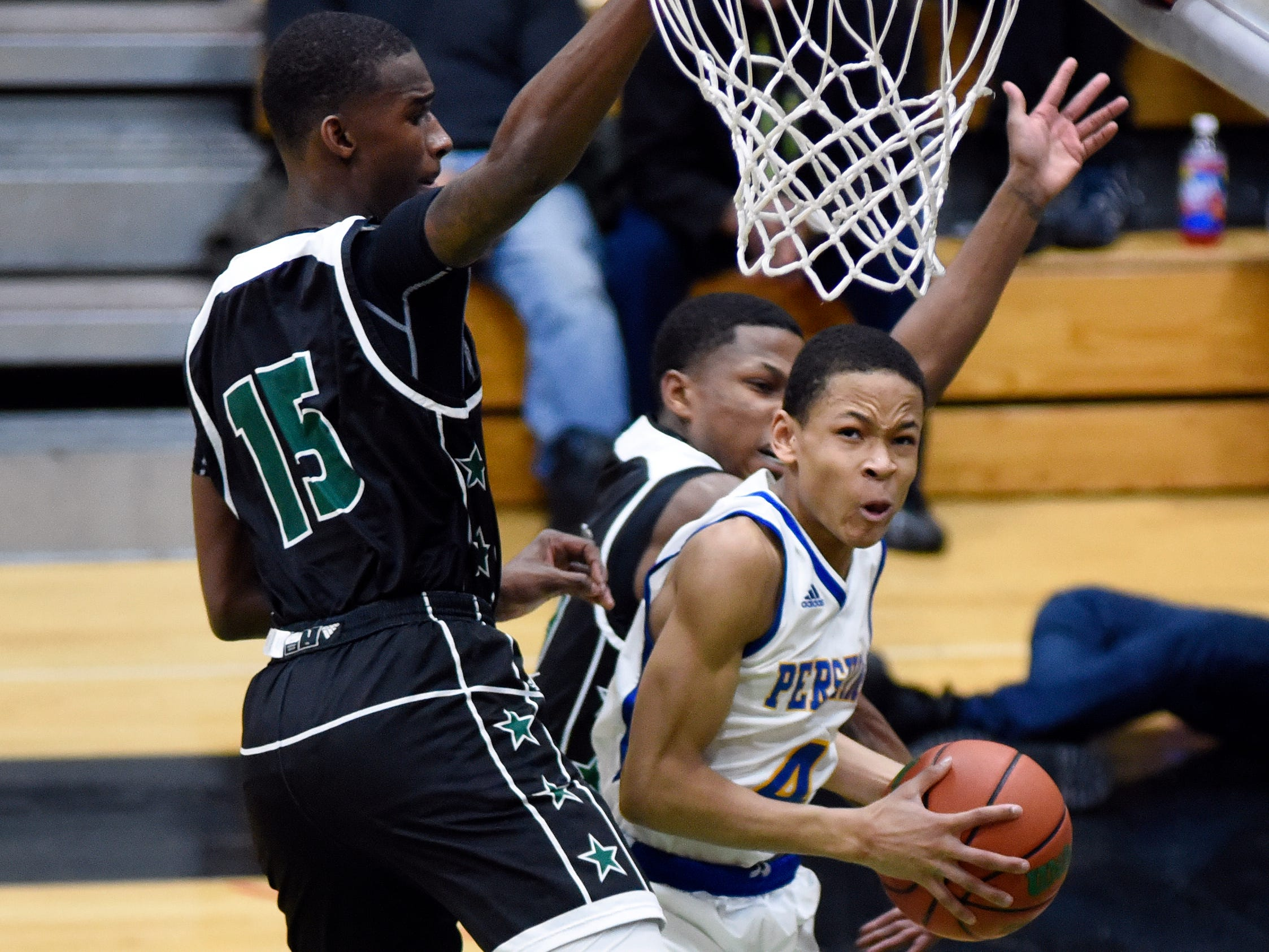 Detroit Pershing's Tharren Hill (4) goes in for a layup as his lane is blocked by Cass Tech's Joshua Harris (during the second quarter, Tuesday, Feb. 12, 2019, in a PSL boys basketball semifinal held at Cass Tech HS in Detroit.  (Jose Juarez/Special to Detroit News)