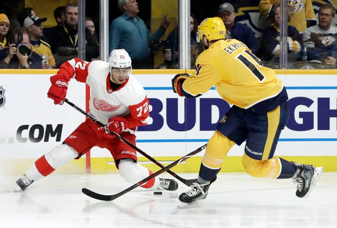 Detroit Red Wings center Andreas Athanasiou (72) moves the puck against Nashville Predators defenseman Mattias Ekholm (14), of Sweden, during the first period of an NHL hockey game Tuesday, Feb. 12, 2019, in Nashville, Tenn.