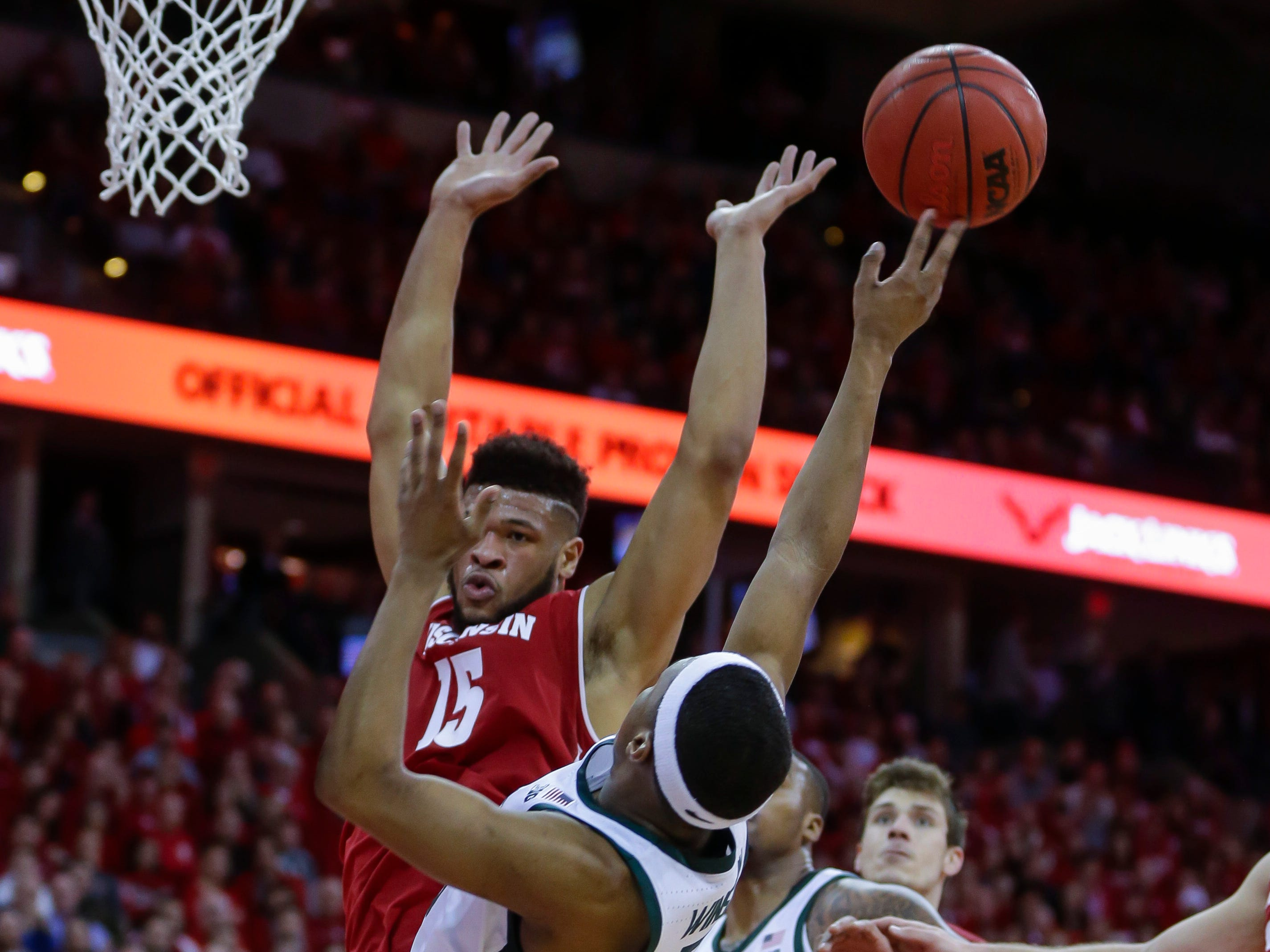 Michigan States's Kyle Ahrens (0) shoots as Wisconsin's Charles Thomas (15) defends during the first half.