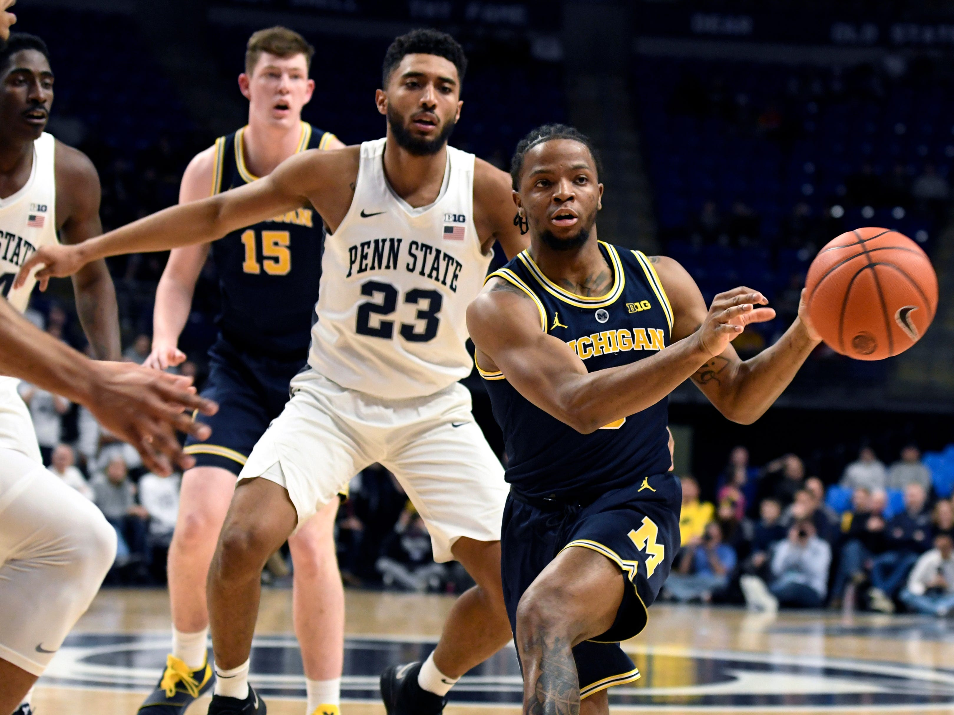 Michigan guard Zavier Simpson (3) passes the ball as Penn State guard Josh Reaves (23) defends during the first half.