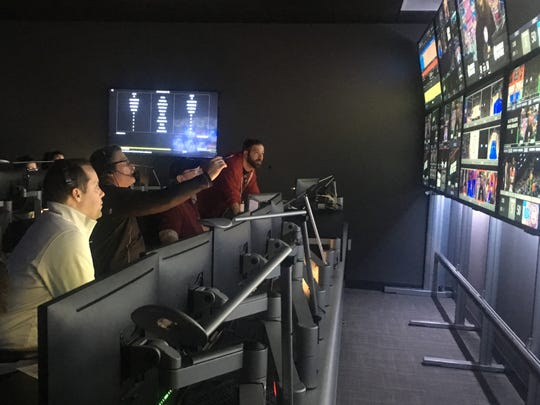 Executive producer Jeremy Smoker, left, and director Jim Sobczak, pointing, direct the action from about 120 choices of different screens in the control room at Little Caesars Arena on Monday, determining what fans see on the giant video board.