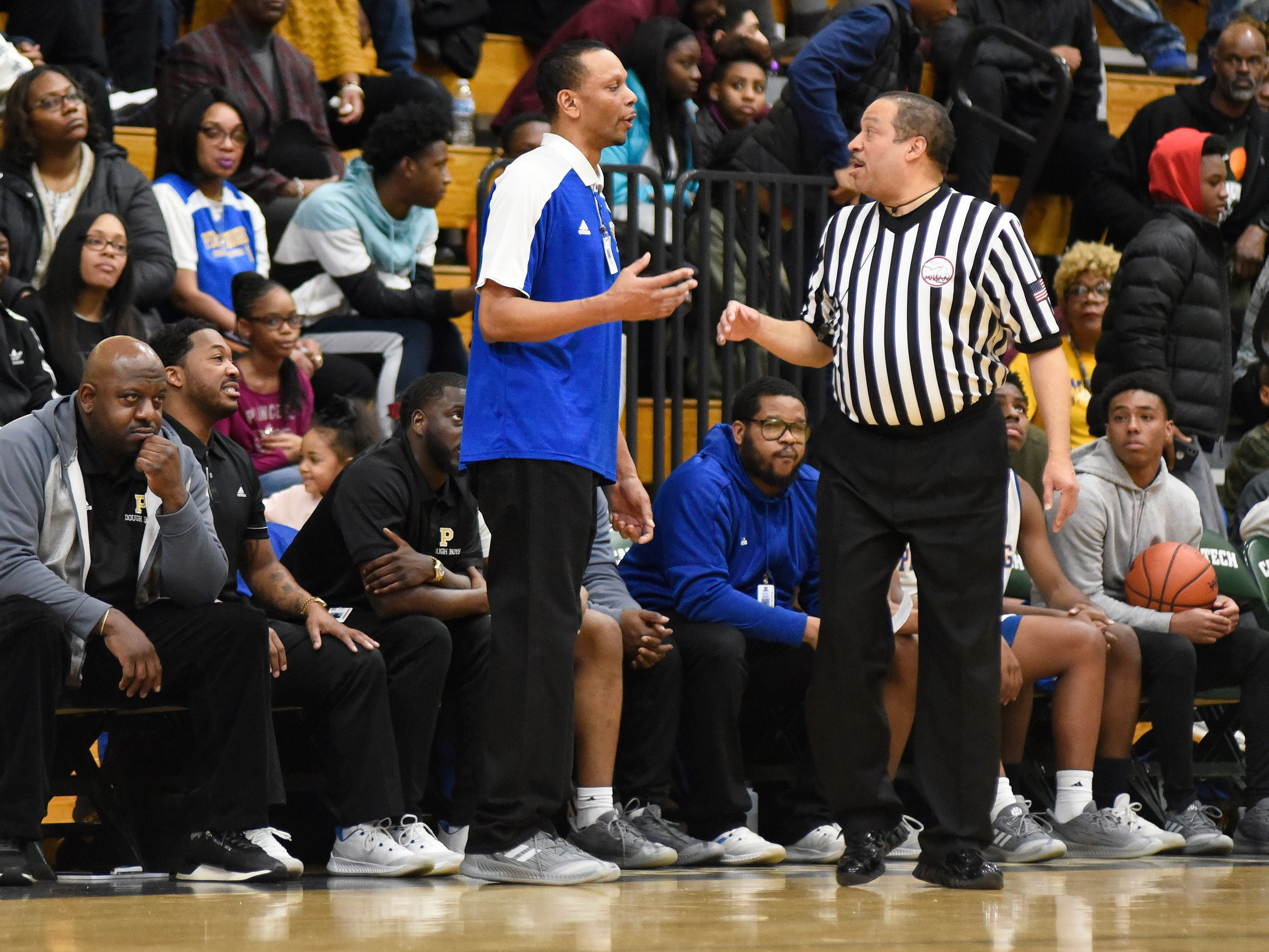 Detroit Pershing boys basketball head coach Shawn Hill, left, argues a call with a referee as his team played against Cass Tech during the fourth quarter.