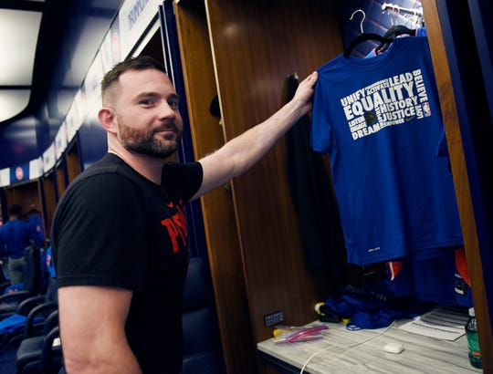 John Coumoundouros, equipment manager, hangs a Black History Month T-shirt in Blake Griffin's locker before Monday's game against the Washington Wizards. He and his staff are responsible for all game-day equipment needs of the players.