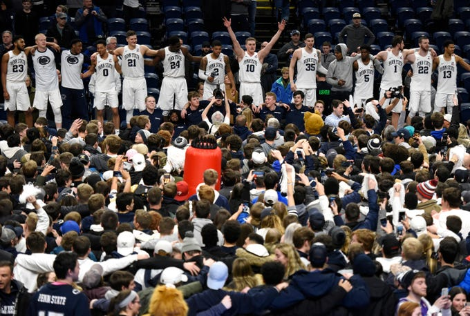 Penn State players celebrate their 75-69 upset win over Michigan after their NCAA college basketball game, Tuesday, Feb. 12, 2019, in State College, Pa.