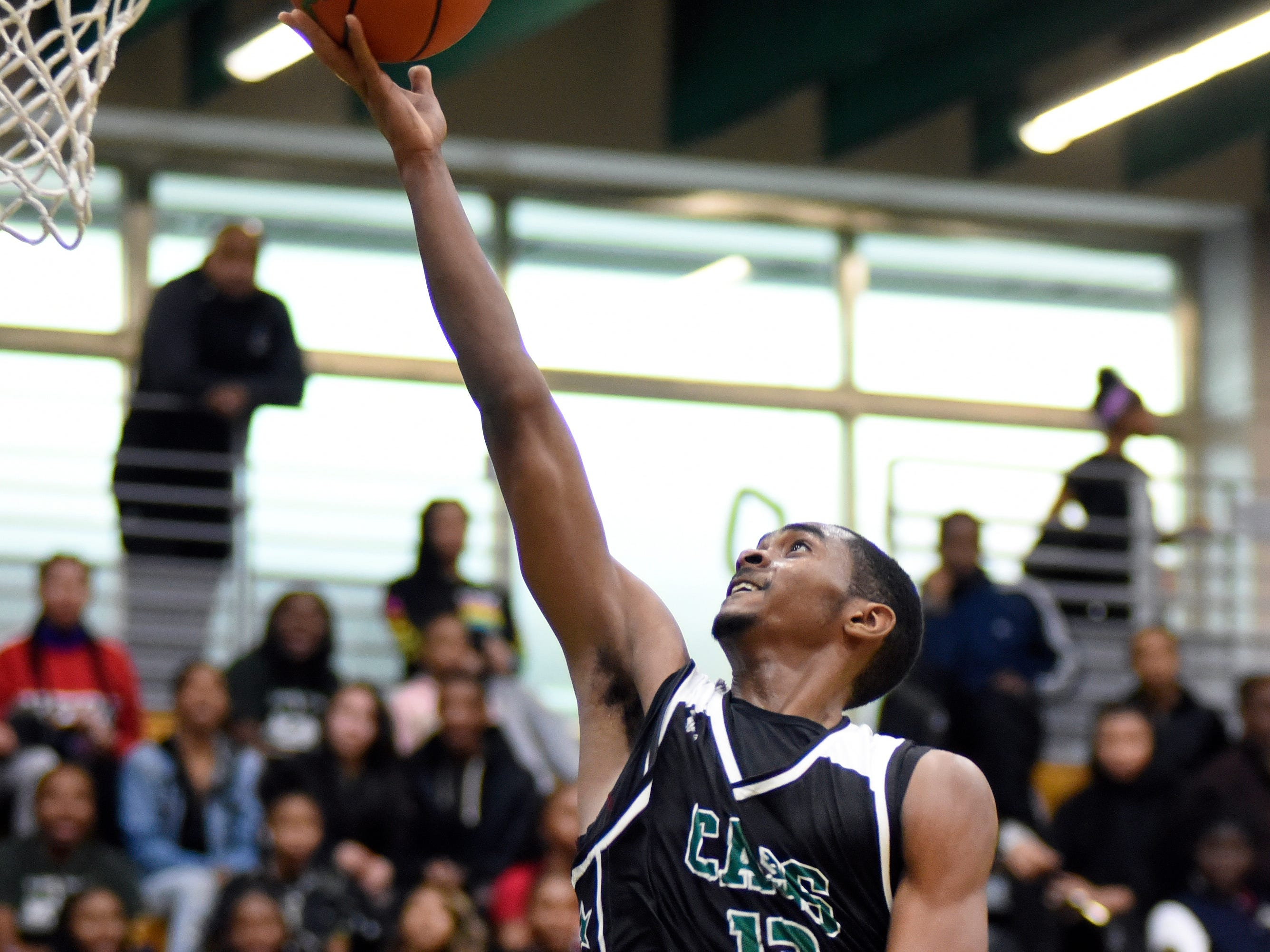 Cass Tech's Kalil Whitehead (13) goes in for a layup attempt against Detroit Pershing during the fourth quarter.