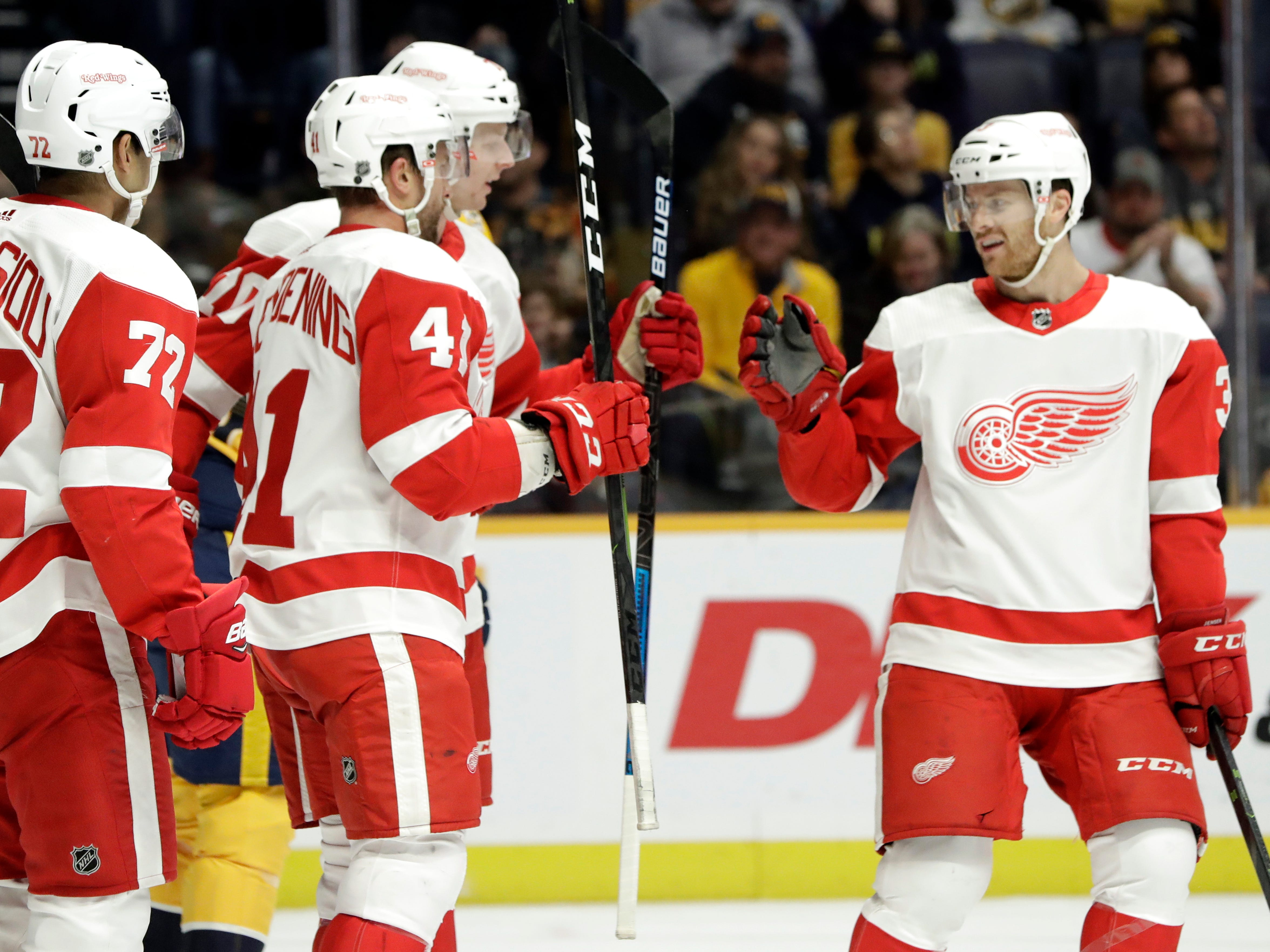 Detroit Red Wings center Luke Glendening (41) celebrates with Nick Jensen (3) and Andreas Athanasiou (72) after Glendening scored a goal against the Nashville Predators during the first period.