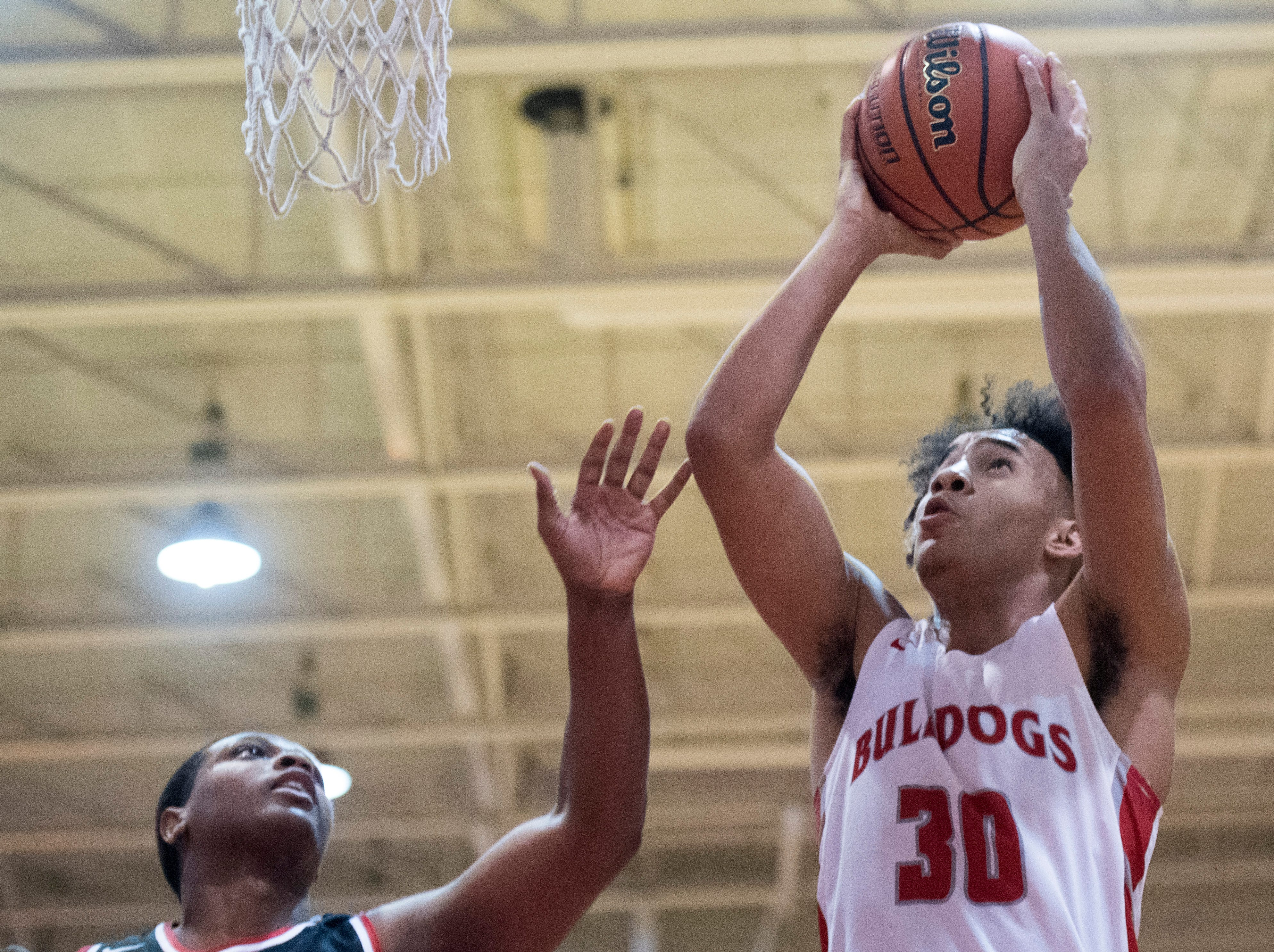 Bosse's Donovan Mcneal (30) takes a shot during the Harrison vs Bosse game at Bosse High School Tuesday, Feb. 12, 2019. The Bosse Bulldogs won 74-56.