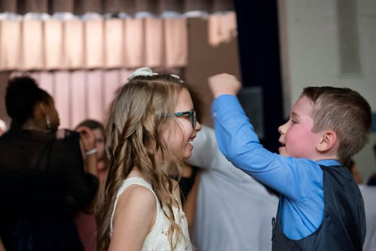 Chance Fullerton, 7, right, measures the height of his friend, Dixie Poindexter, 7, on the dance floor at the Caze Elementary School Sweetheart Dance Tuesday night. The two spent most of the dance together running, jumping, dancing and almost always laughing.