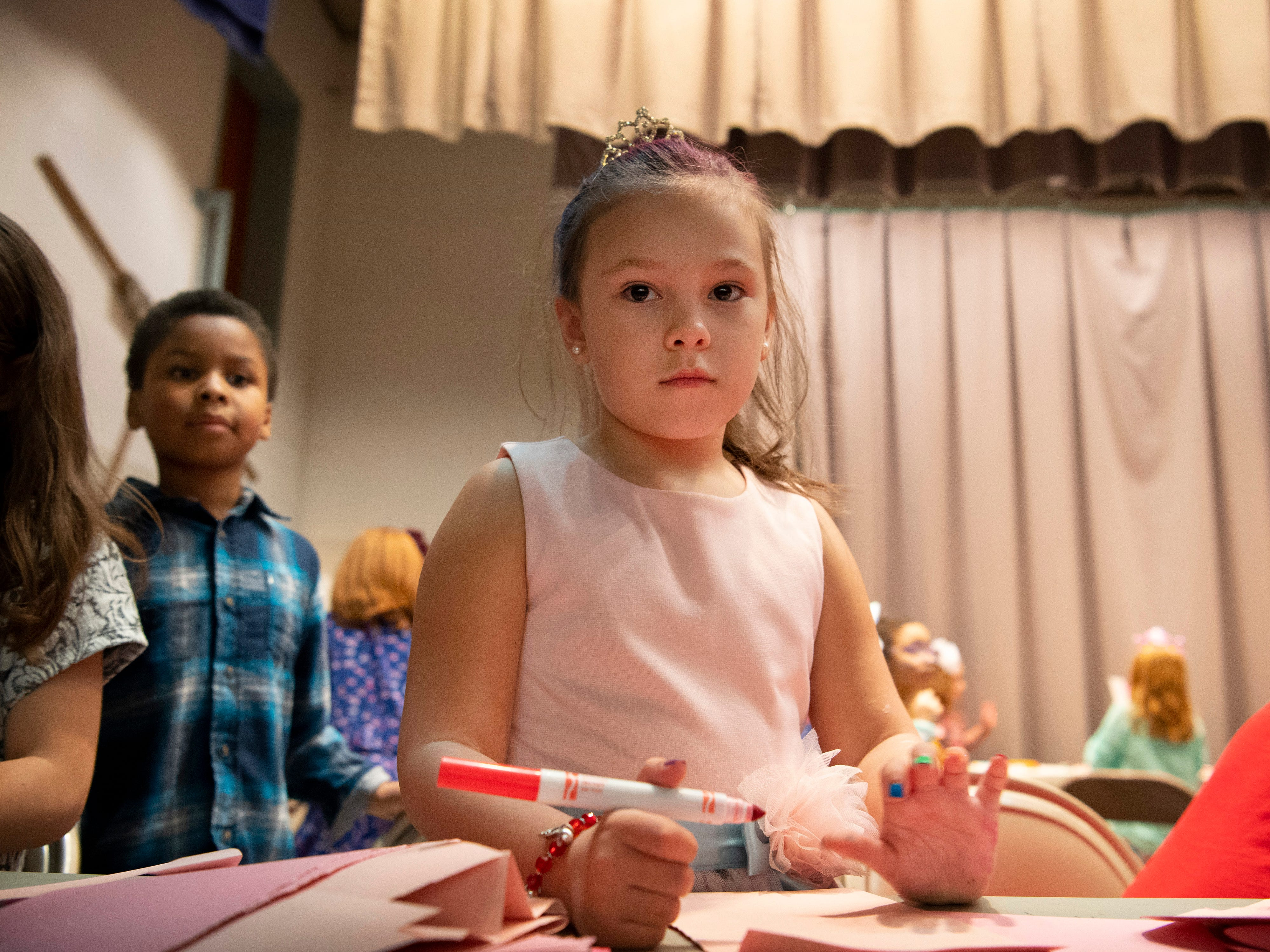 Lilliana Gonzales, 6, creates valentines on the Caze Elementary School stage during the Sweetheart Dance Tuesday night.