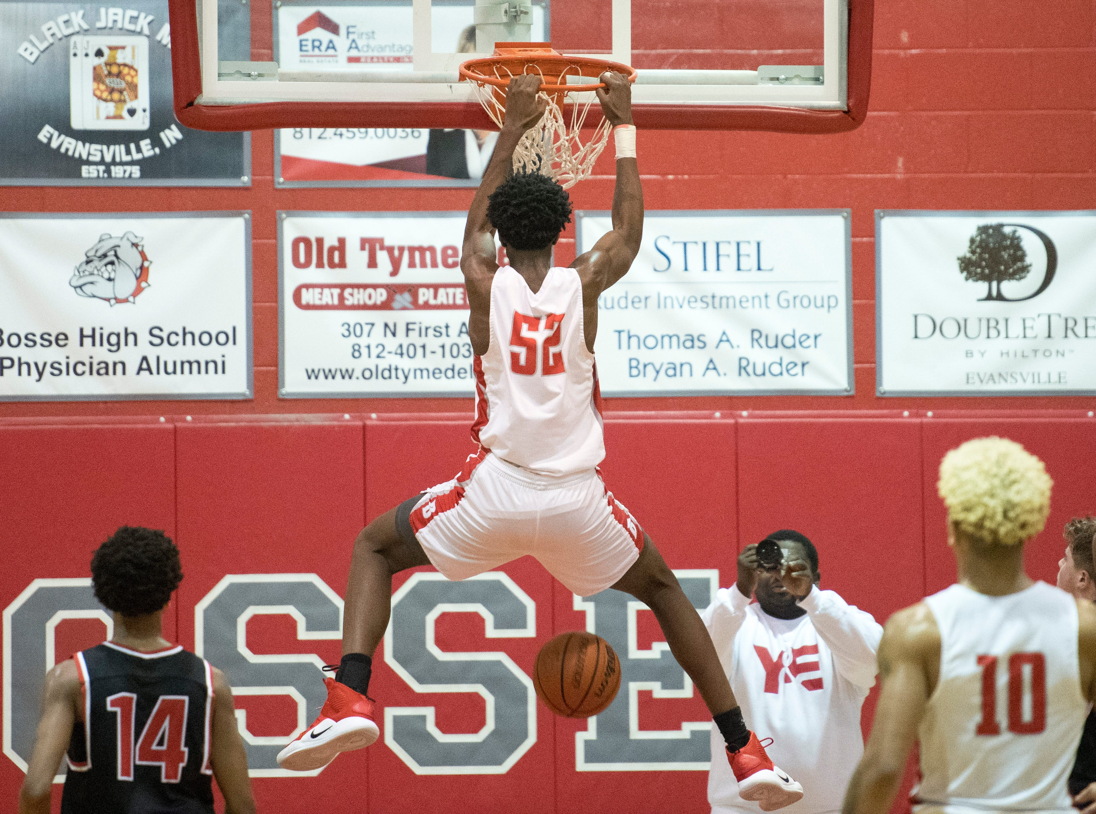 Bosse's Kiyron Powell (52) hangs from the rim after dunking the ball during the Harrison vs Bosse game at Bosse High School Tuesday, Feb. 12, 2019. The Bosse Bulldogs won 74-56.