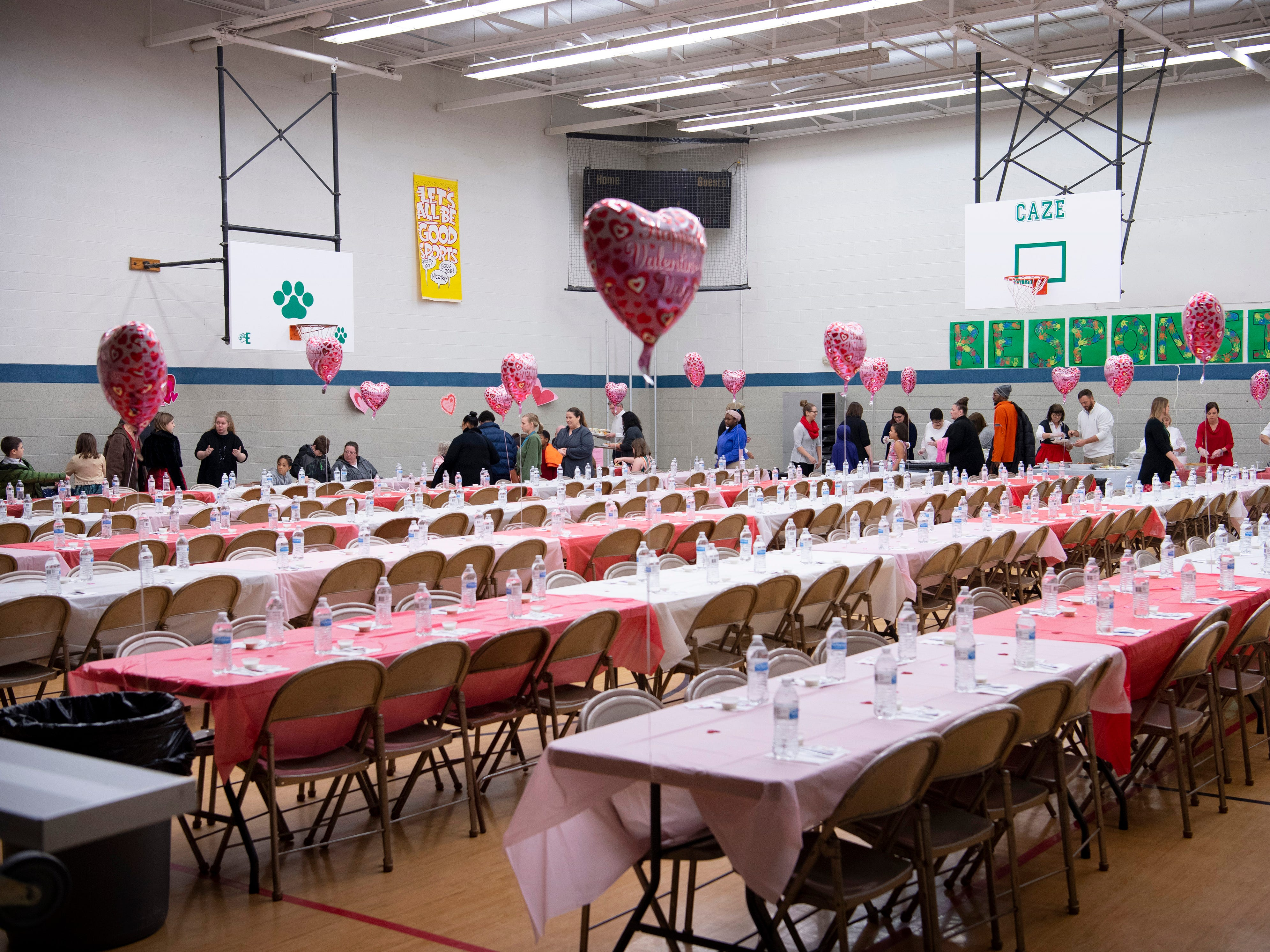 Attendees begin to file in to the Sweetheart Dance at Caze Elementary School Tuesday night. The night started with a dinner of pasta, salad and cupcakes and moved quickly into Valentine's Day crafts and dancing.