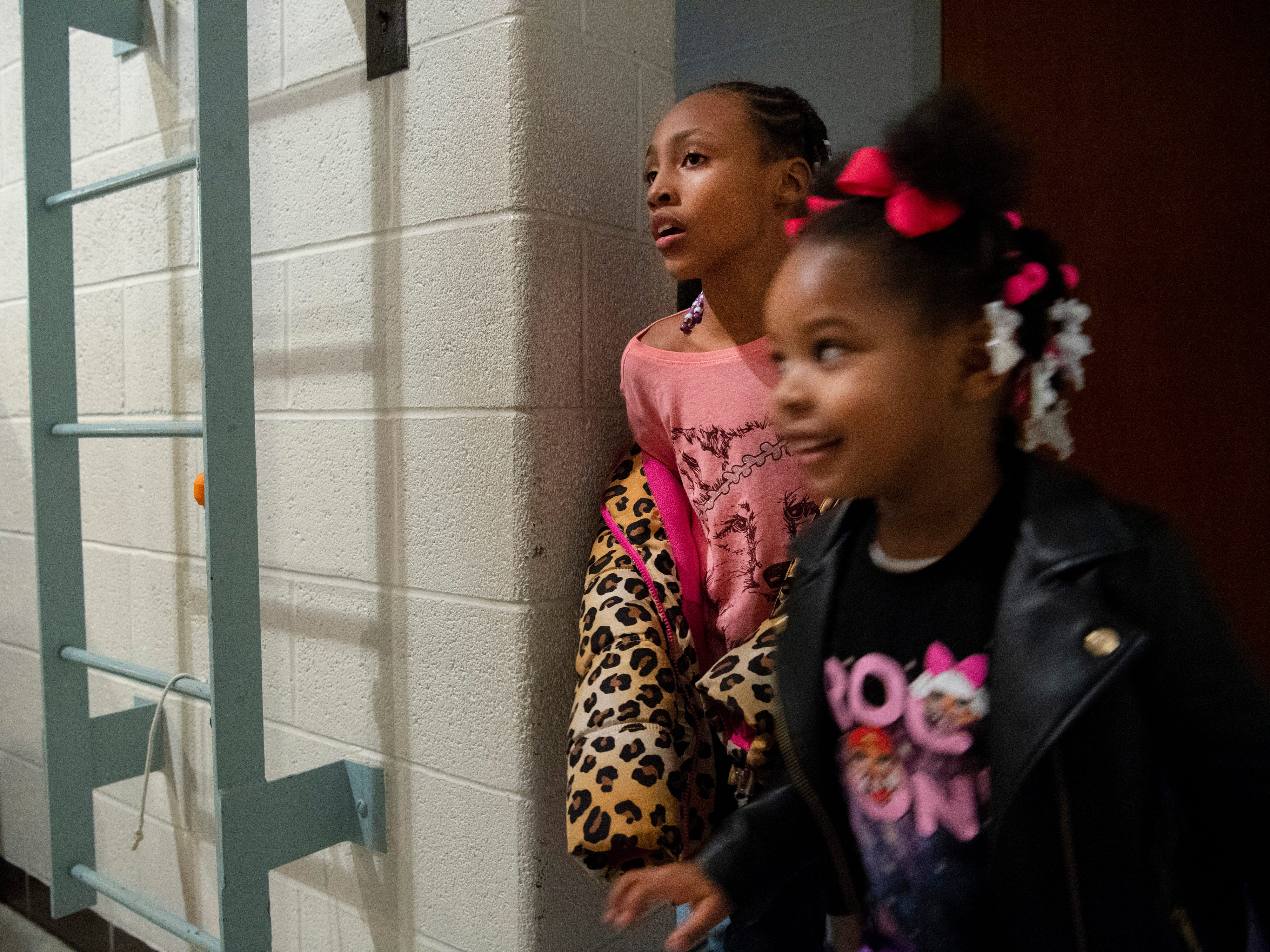 Aysia Hall, 8, top, and Adria Wiley, 4, round the corner backstage at Caze Elementary School to find the crafting area onstage at the Sweetheart Dance Tuesday night.