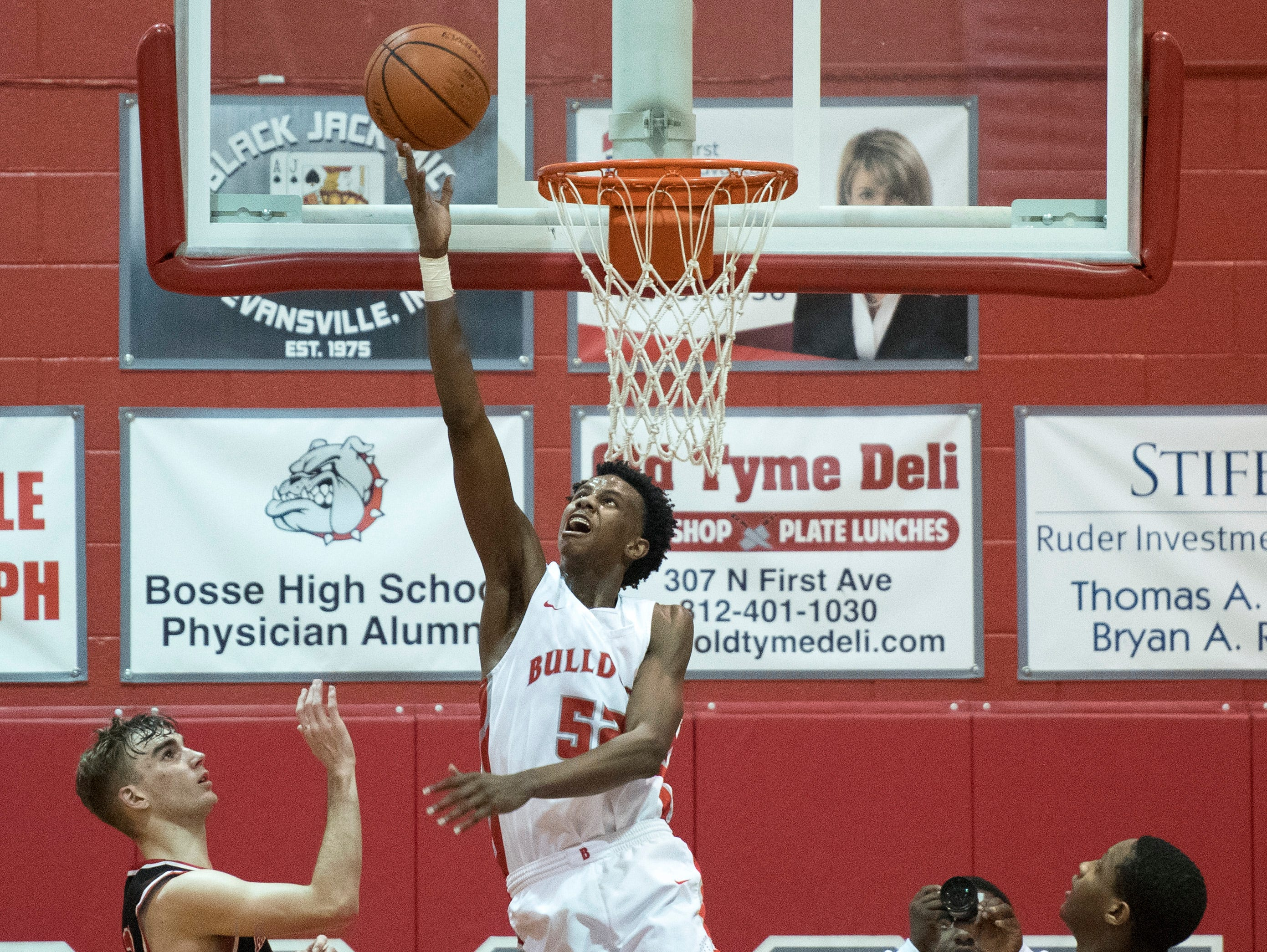 Bosse's Kiyron Powell (52) takes a shot from behind the net during the Harrison vs Bosse game at Bosse High School Tuesday, Feb. 12, 2019. The Bosse Bulldogs won 74-56.