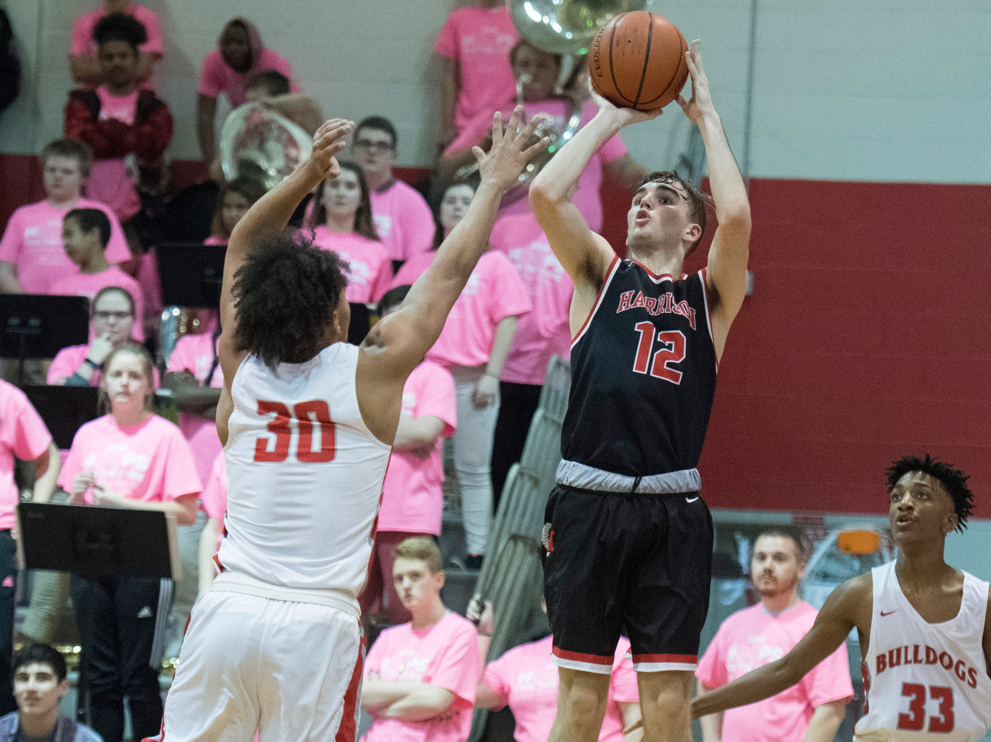 Harrison's Mason Bost (12) takes a 3-point shot during the Harrison vs Bosse game at Bosse High School Tuesday, Feb. 12, 2019. The Bosse Bulldogs won 74-56.