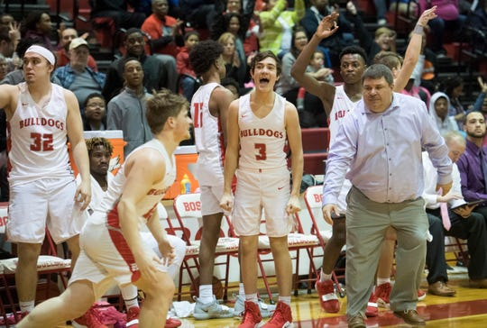 The Bosse Bulldogs bench erupts after Bosse's Kolten Sanford (45) sinks a 3-pointer during the Harrison vs Bosse game at Bosse High School Tuesday, Feb. 12, 2019. The Bosse Bulldogs won 74-56.