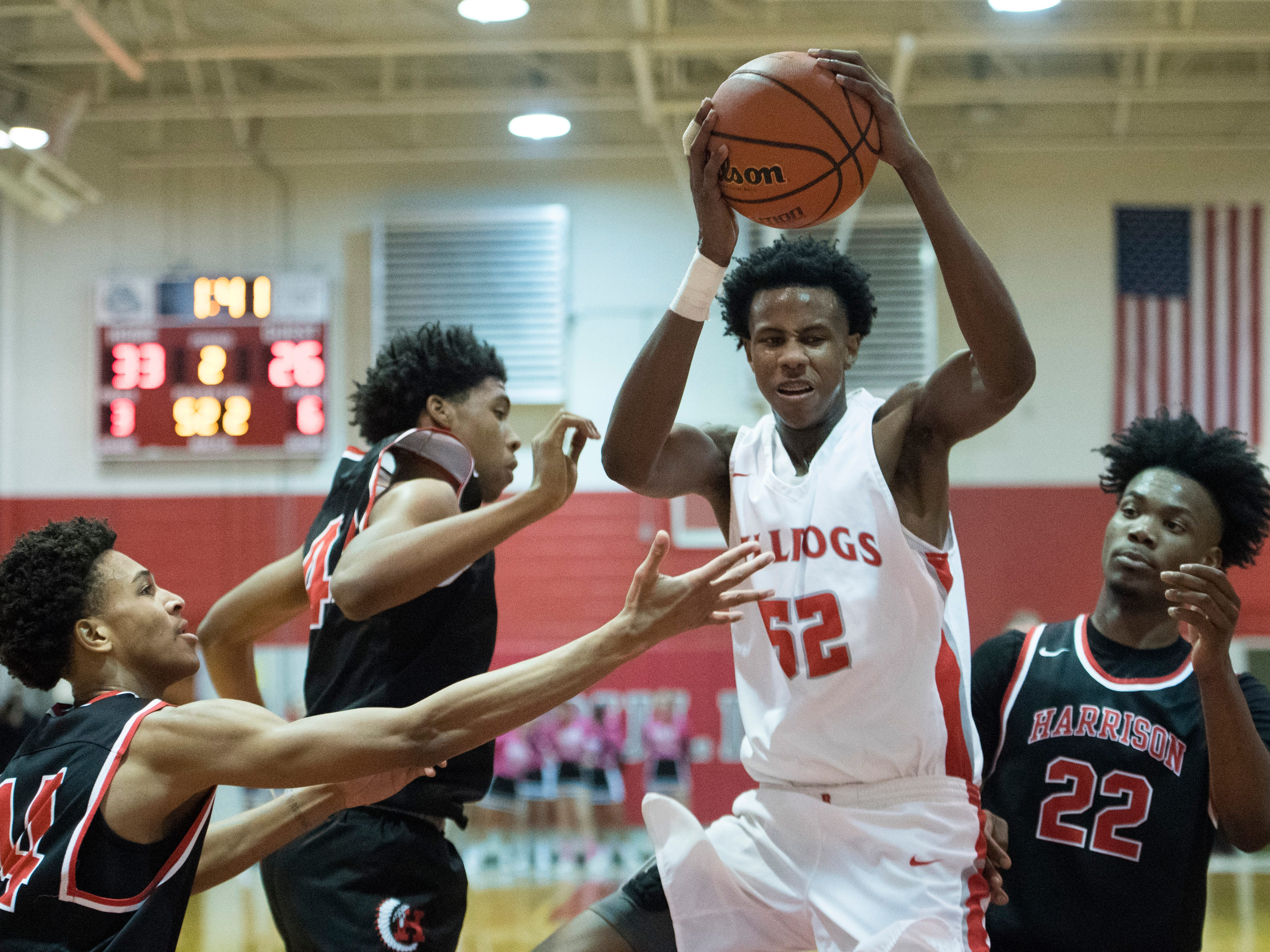 Bosse's Kiyron Powell (52) pulls down a rebound in the first half of the Harrison Warriors vs Bosse Bulldogs game at Bosse High School Tuesday, Feb. 12, 2019.