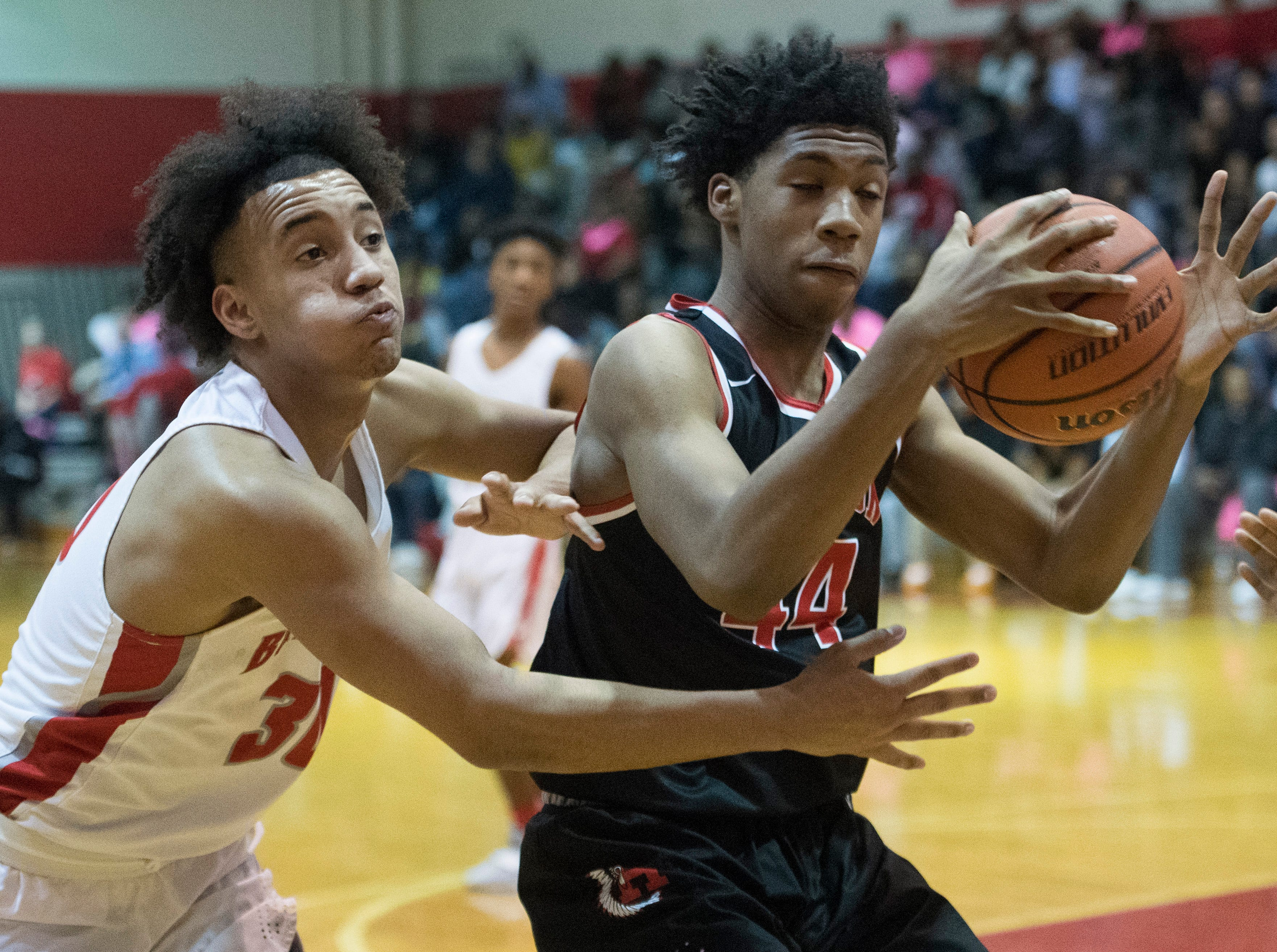 Bosse's Donovan Mcneal (30) attempted to steal the ball from Harrison's Terrence Ringo (44) during the Harrison vs Bosse game at Bosse High School Tuesday, Feb. 12, 2019.