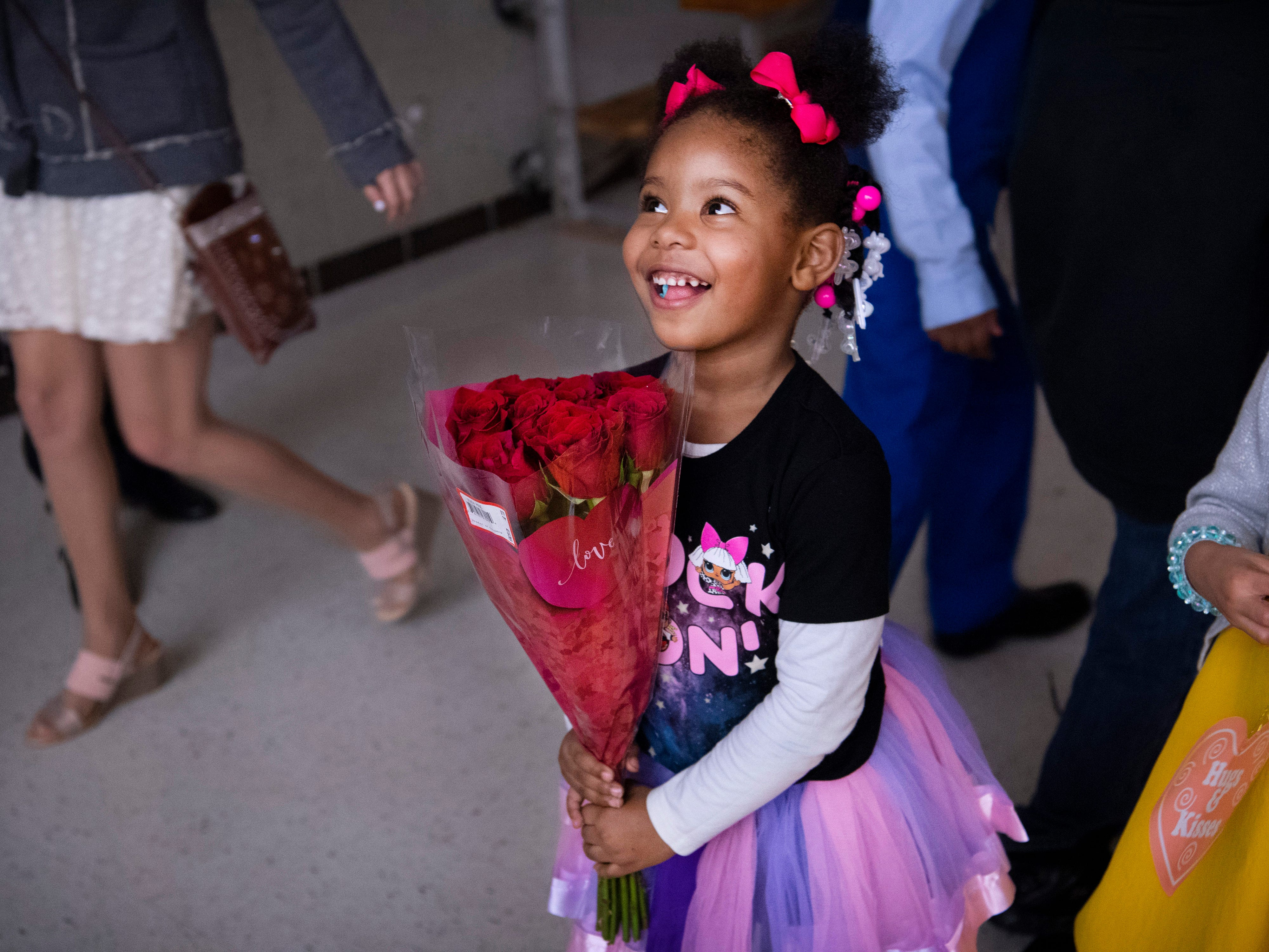 Adria Wiley, 4, a student in the pre-kindergarten program at Caze Elementary School, parades through the gymnasium clutching the red roses her dad had given her at the Sweetheart Dance Tuesday night. The annual Valentine's Day celebration offers students and their families a night of  community caring... not to mention a wonderful meal, crafting and dancing.