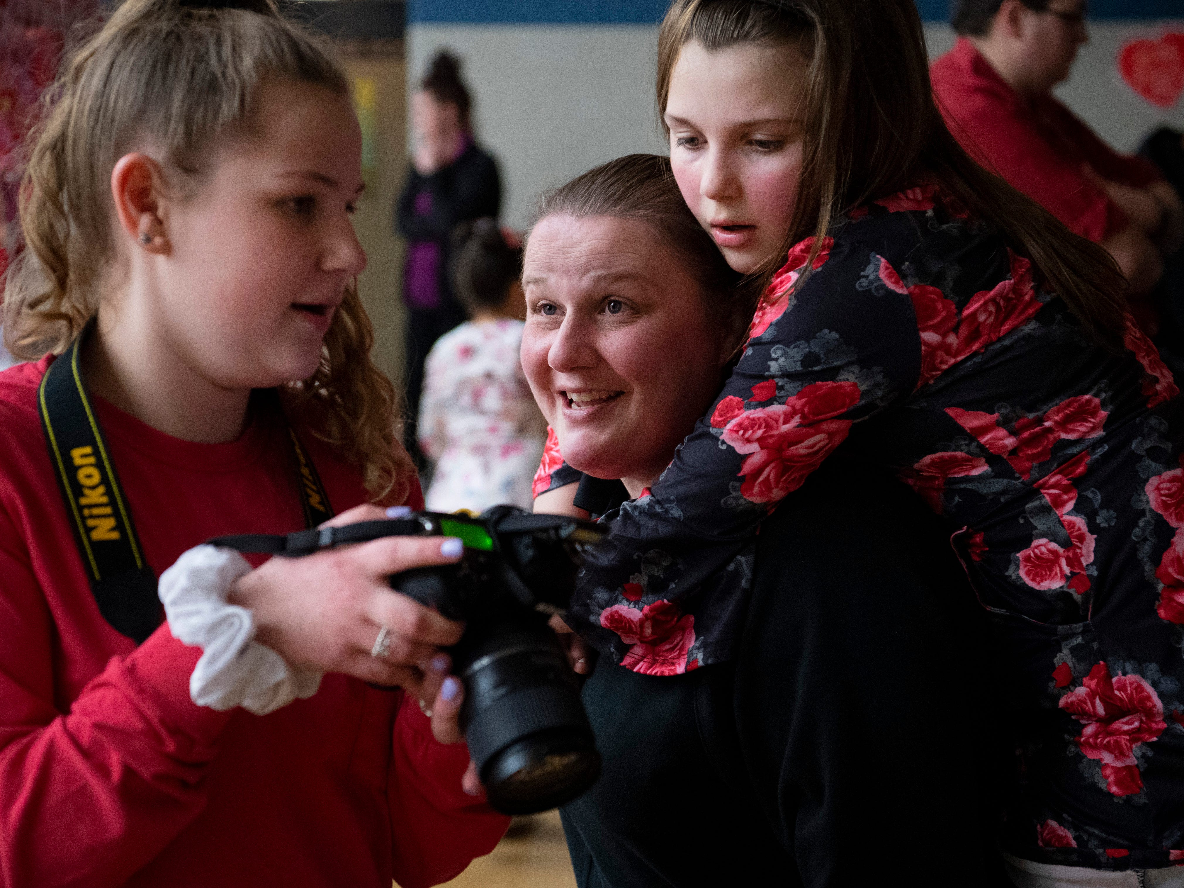 Lilly Osborne, 15, left, shares a picture she made of her aunt, Lori Briggeler, center, and sister, Caze Elementary School student Kayla Osborne, 10, at the Sweetheart Dance Tuesday night. Lilly was once a student at Caze and was volunteering her photographic services to help make the night as special for them as it was for her.