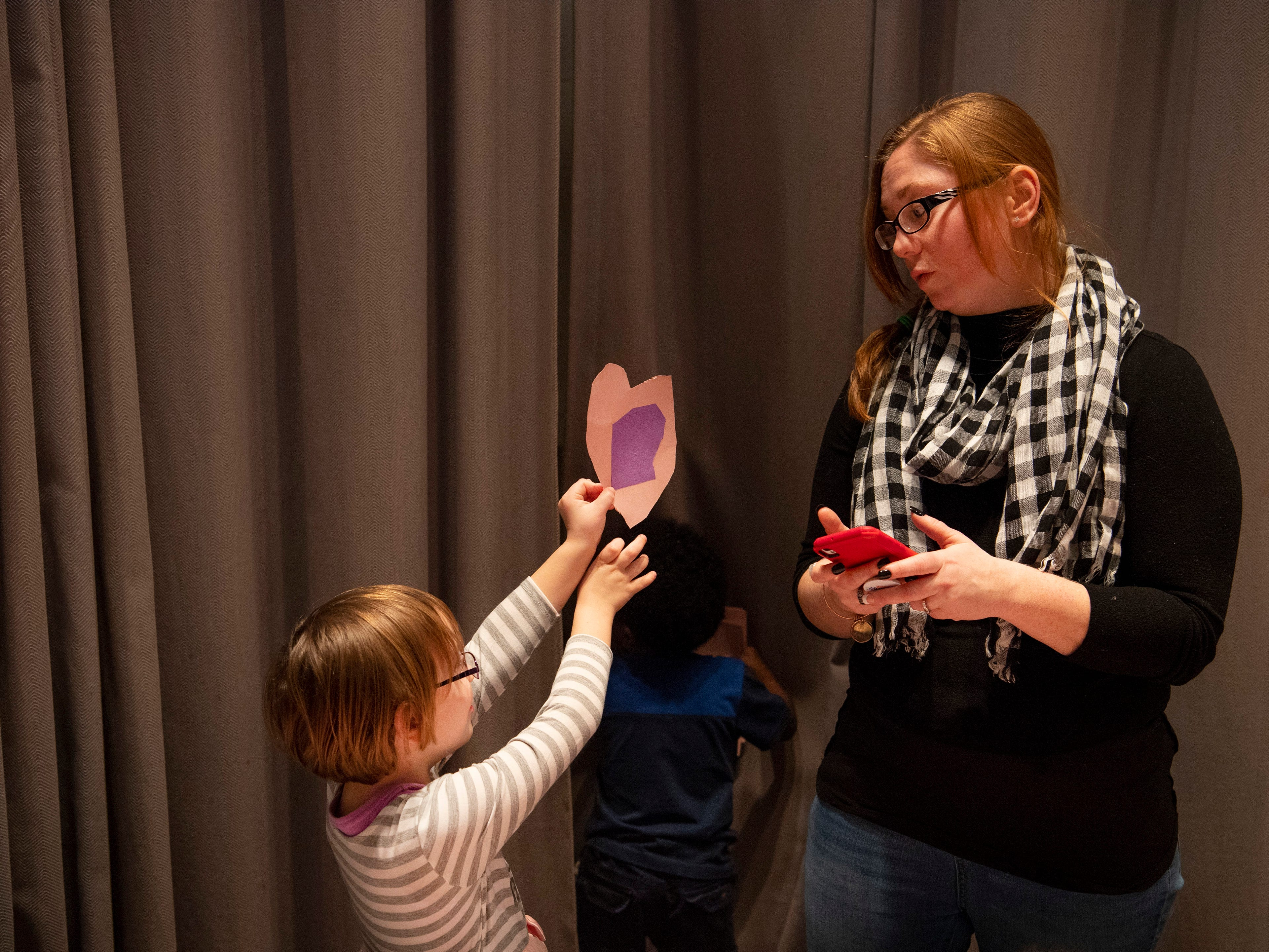Charlotte Oldhamsharp, 5, presents her mom, Jesika, the construction paper valentine she created at the Sweetheart Dance at Caze Elementary School Tuesday night.