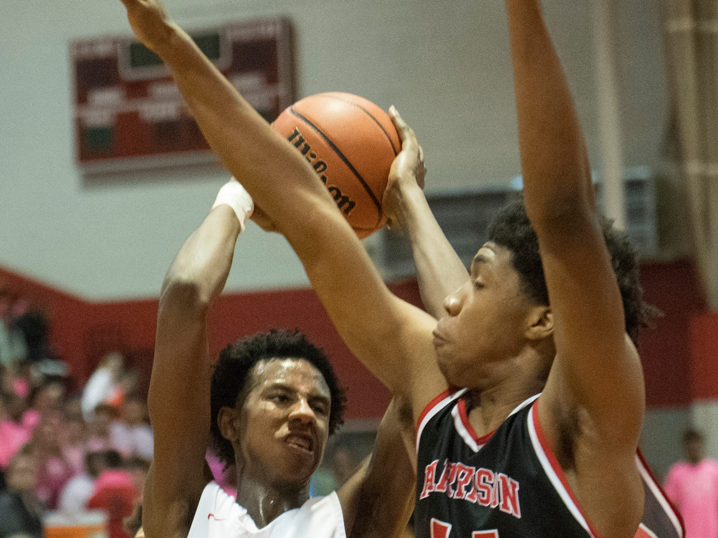 Bosse's Kiyron Powell (52) is forced back by Harrison's Terrence Ringo (44) but fires off a shot during the Harrison vs Bosse game at Bosse High School Feb. 12, 2019. Bosse won