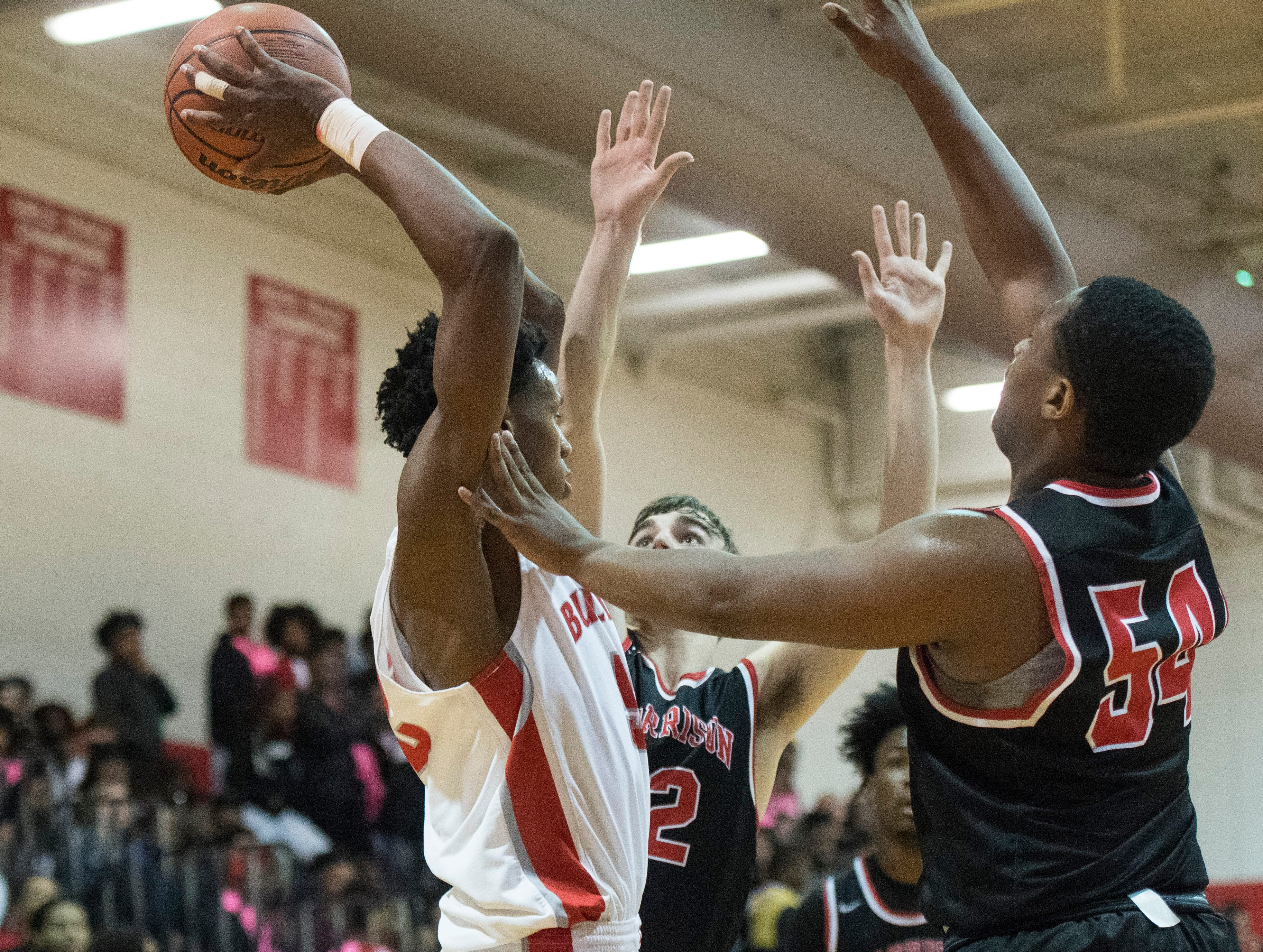 Bosse's Kiyron Powell (52) passes the ball after being overwhelmed by Warrior defense during the Harrison vs Bosse game at Bosse High School Tuesday, Feb. 12, 2019.