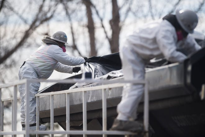 Crews in hazardous material suits cover a truckload of debris in thick plastic as they work to demolish a house and garage deemed to be posing a public safety threat to the surrounding neighborhood due in part to hazardous levels of methamphetamines on Wednesday, Feb. 13, 2019, in Loveland, Colo.