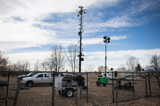 A Larimer County  Department employee works on a mobile security camera station as crews work to demolish a house and garage deemed to be posing a public safety threat to the surrounding neighborhood due in part to hazardous levels of methamphetamines on Wednesday, Feb. 13, 2019, in Loveland, Colo.
